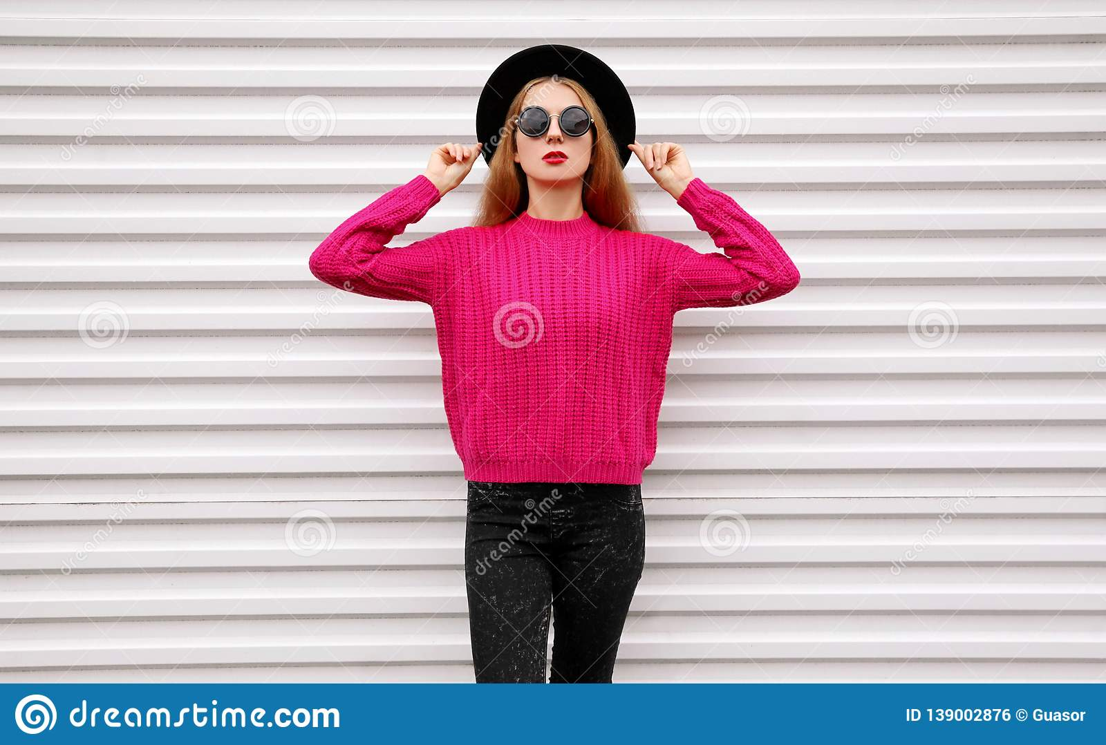Stylish pretty woman model posing in colorful pink knitted sweater, black round hat on white wall