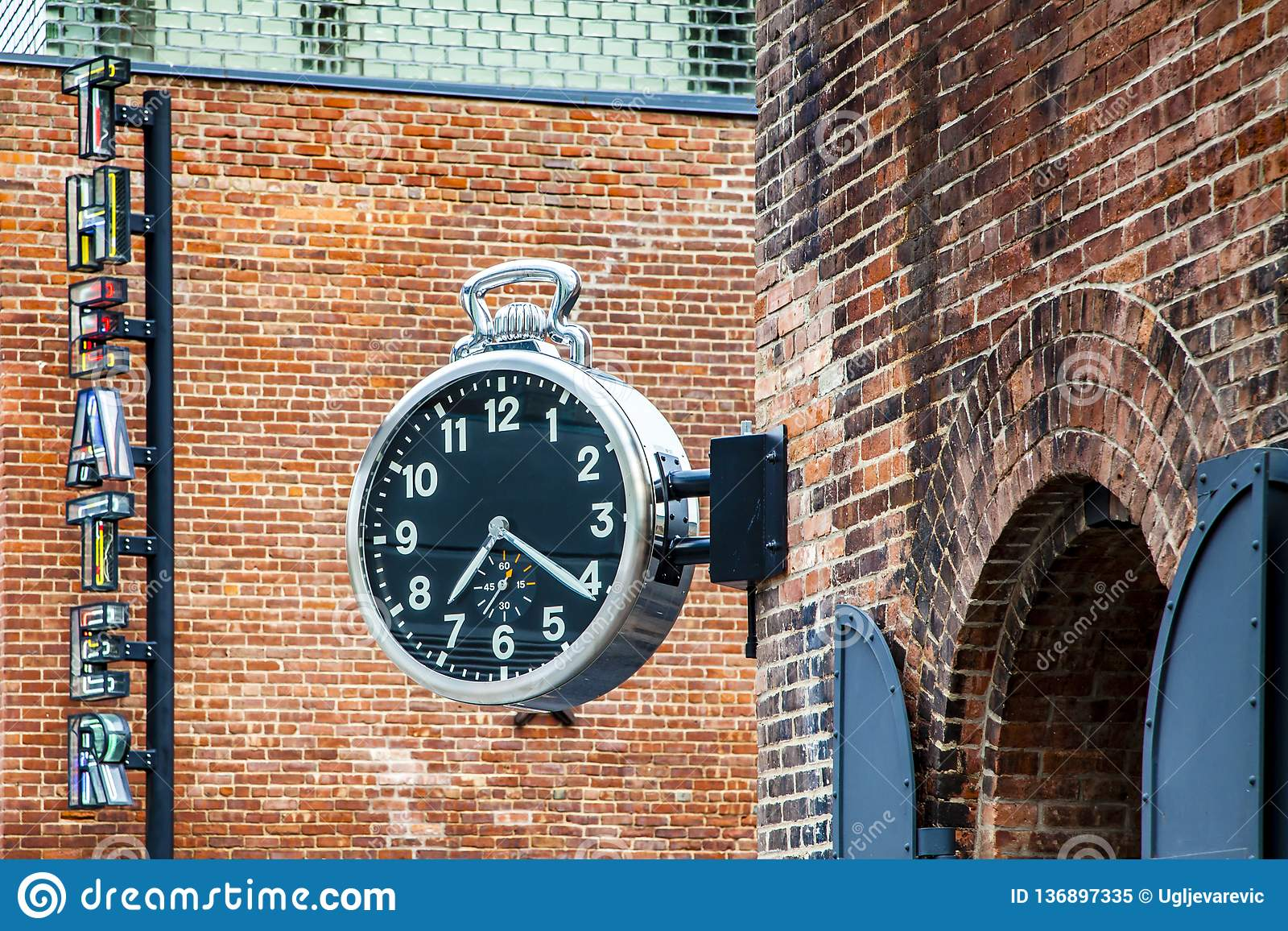 Stylish Public Analog Clock Hanging On Brick Wall Showing Time In