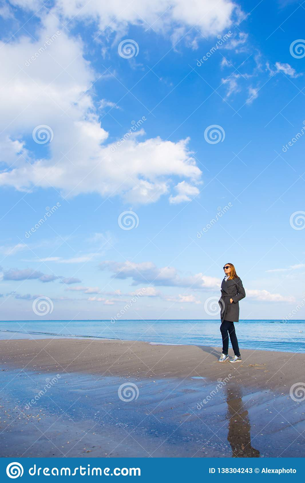 Stylish red-haired girl in dark coat and sunglasses standing on seaside with beautiful sky and water on background