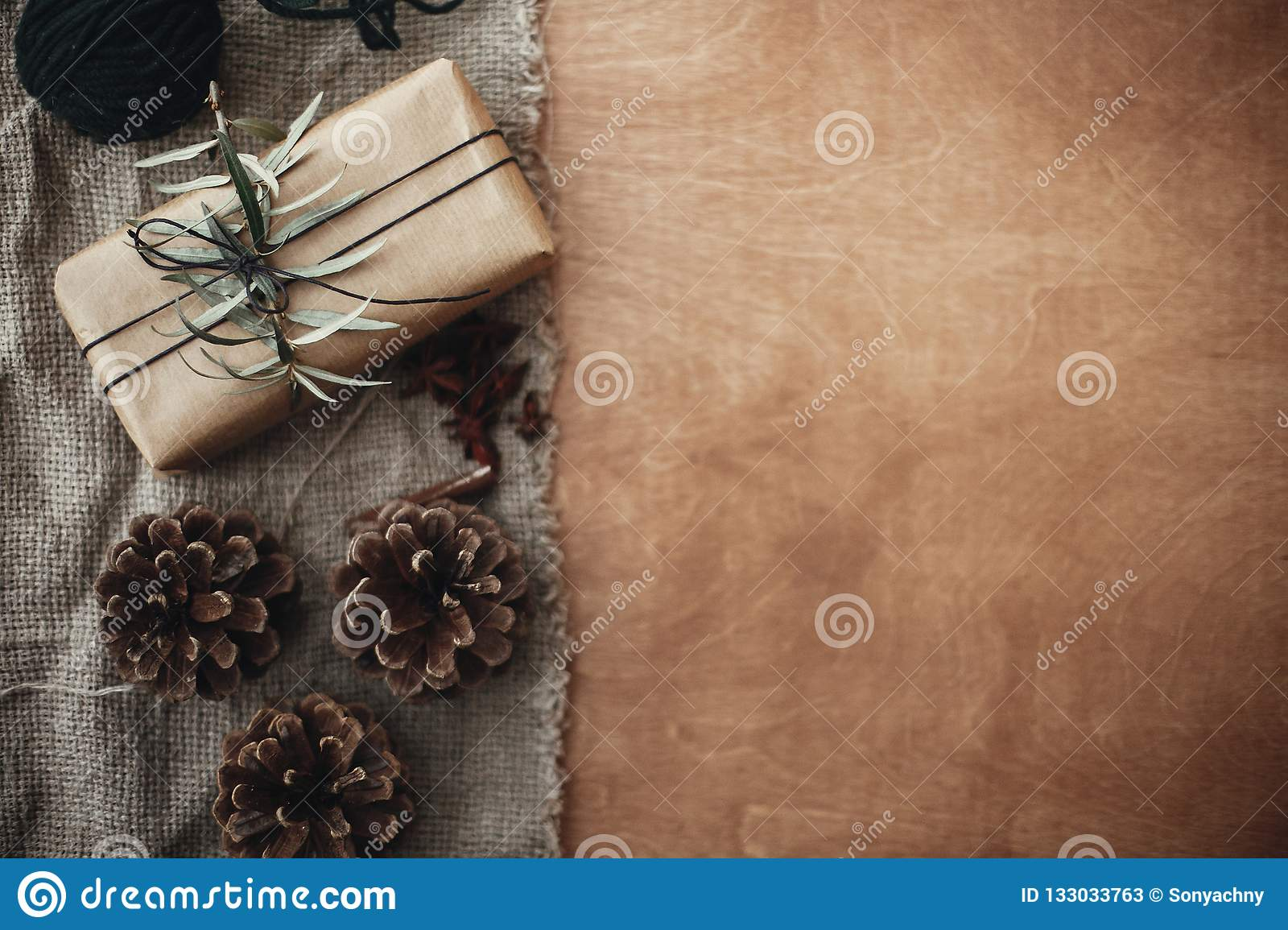 Stylish rustic gift box with green branch and fir branches, anise, pine cones, cinnamon on rustic wooden background. Simple eco p