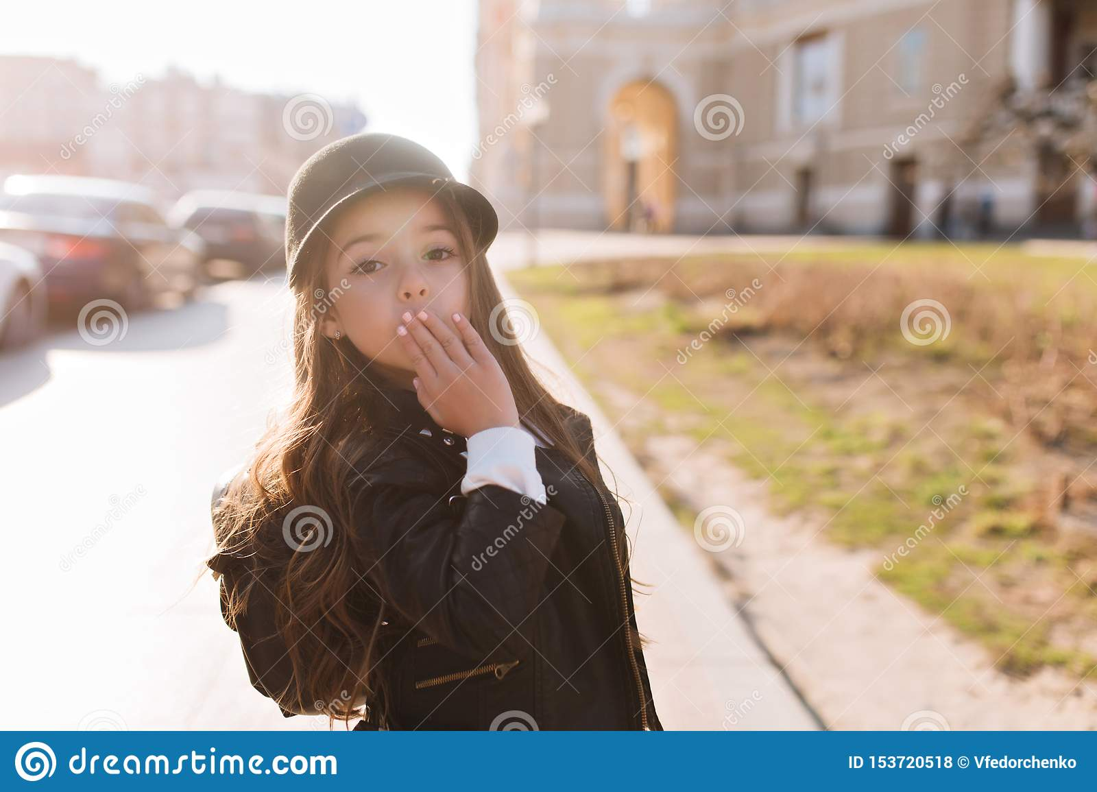Stylish schoolgirl going home after classes, wearing backpack and trendy black hat. Portrait of surprised little girl