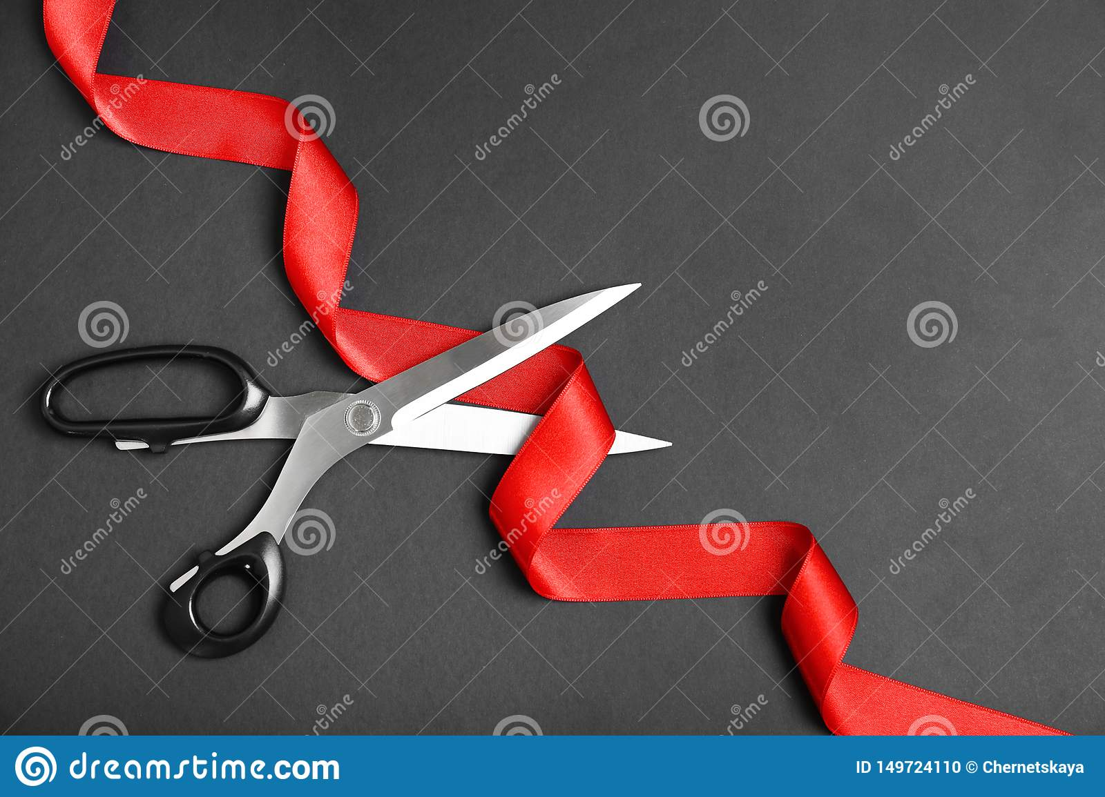 Stylish scissors and red ribbon on black background, flat lay. Ceremonial tape cutting