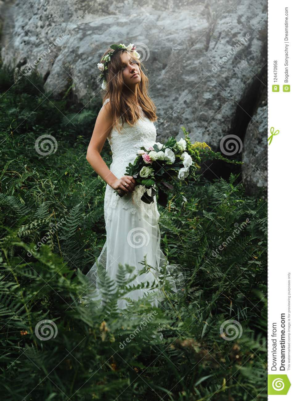 Stylish sensual bohemian bride in a fairytale with bouquet on background of rocks in mountains