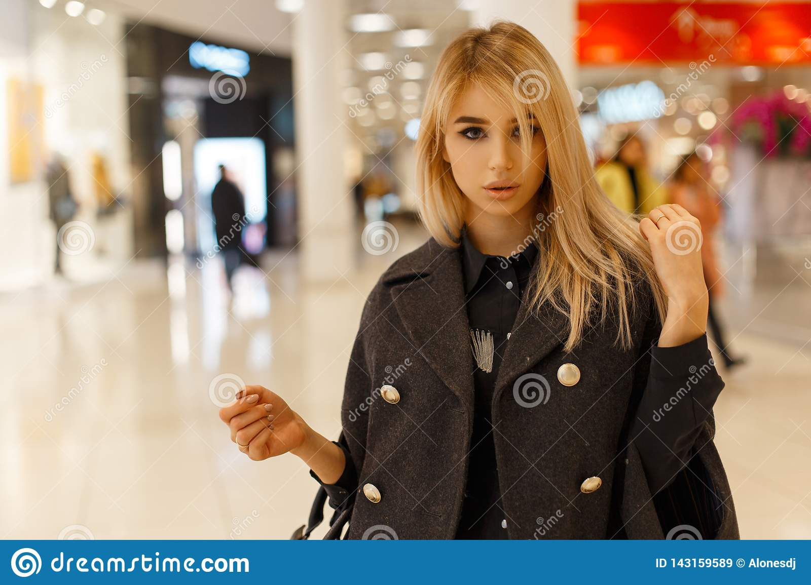 Stylish sexy young blond woman with gray eyes in a stylish gray coat in a black trendy shirt with a leather black handbag