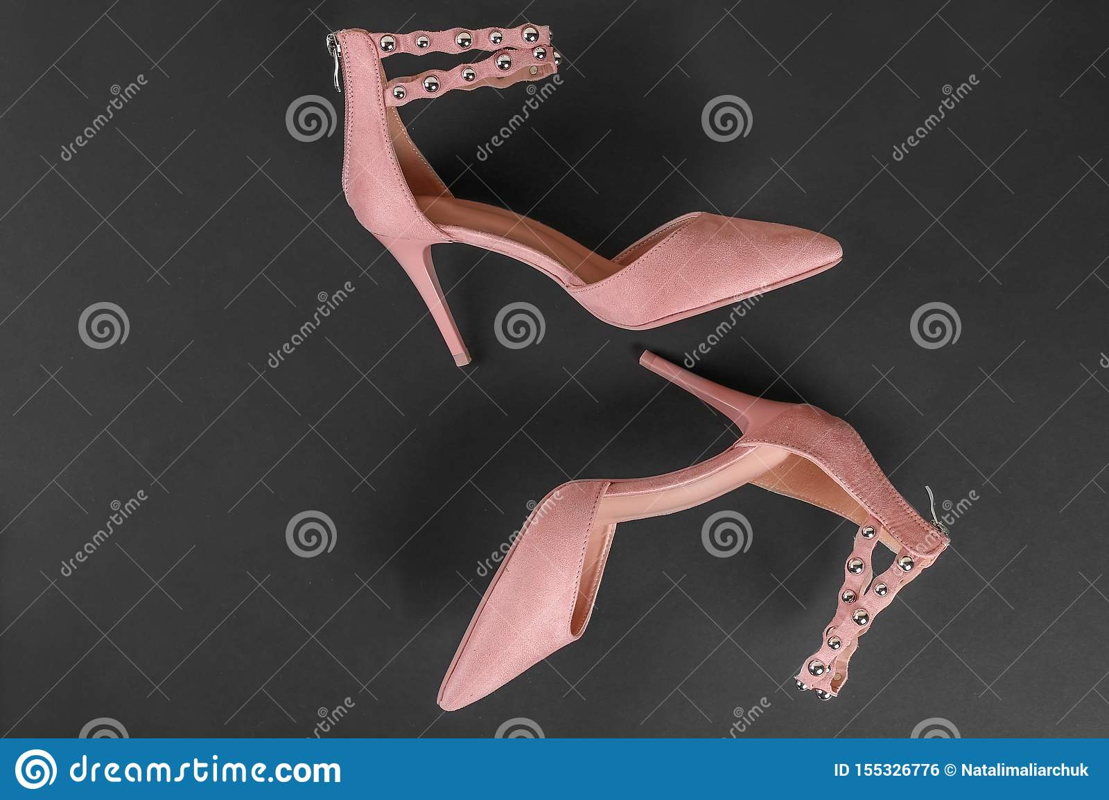 Stylish summer sandals of pastel color on black background, close up. Top view. Flat lay