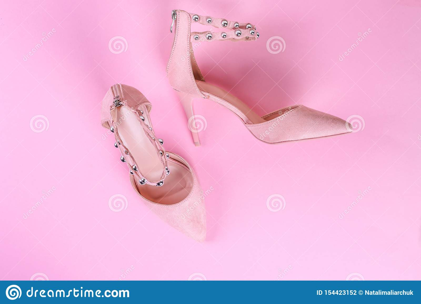 Stylish summer sandals of pastel color isolated on pink background, close up. Top view. Flat lay