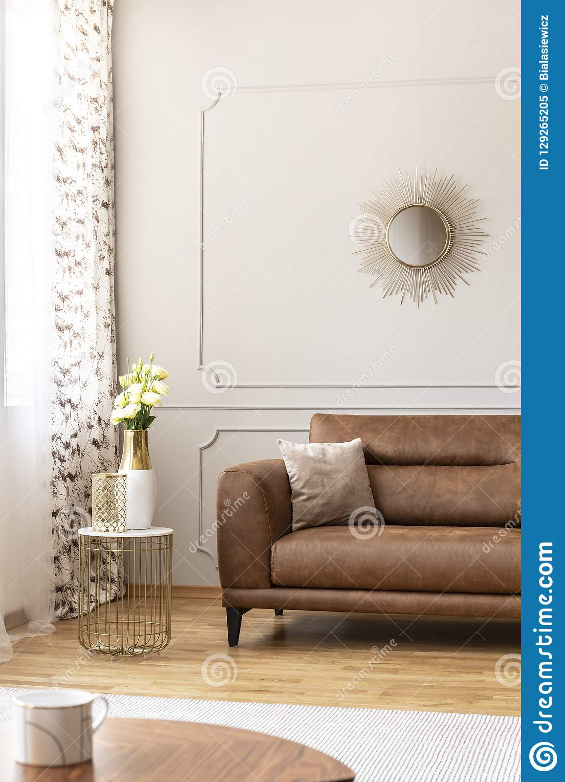 Stylish table with vase with flowers on it next to comfortable leather couch with beige pillow in luxury living room interior