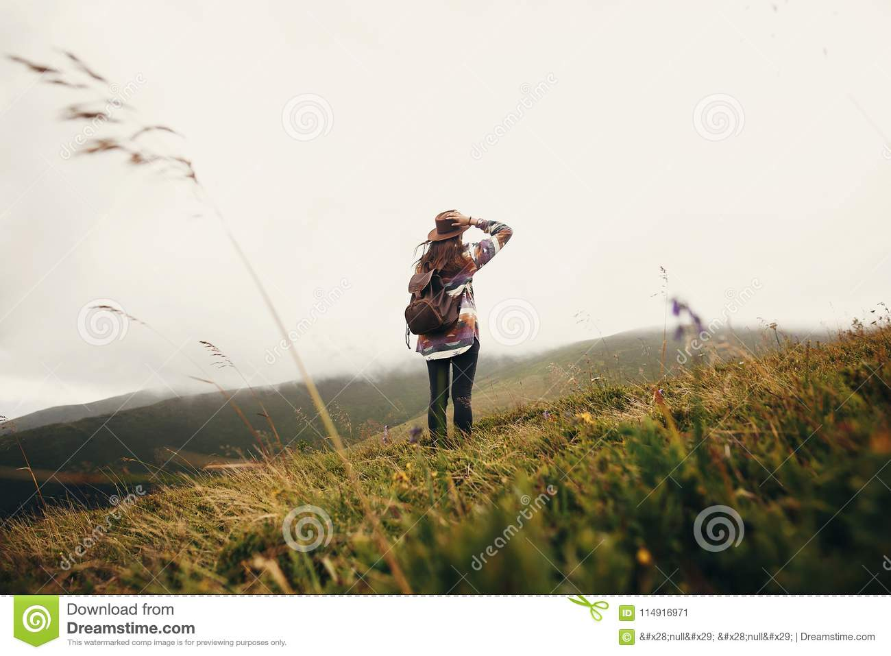 Stylish traveler girl holding hat with backpack and windy hair i