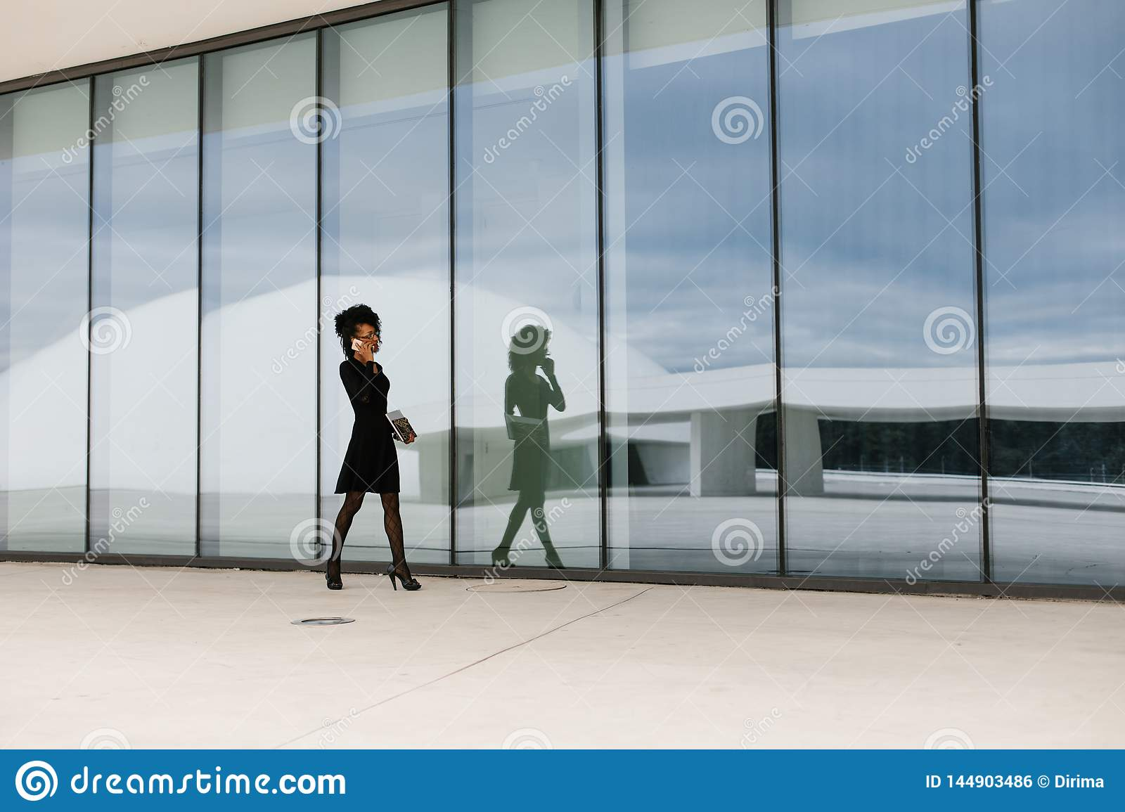 Professional woman walking and talking on cellphone outside.