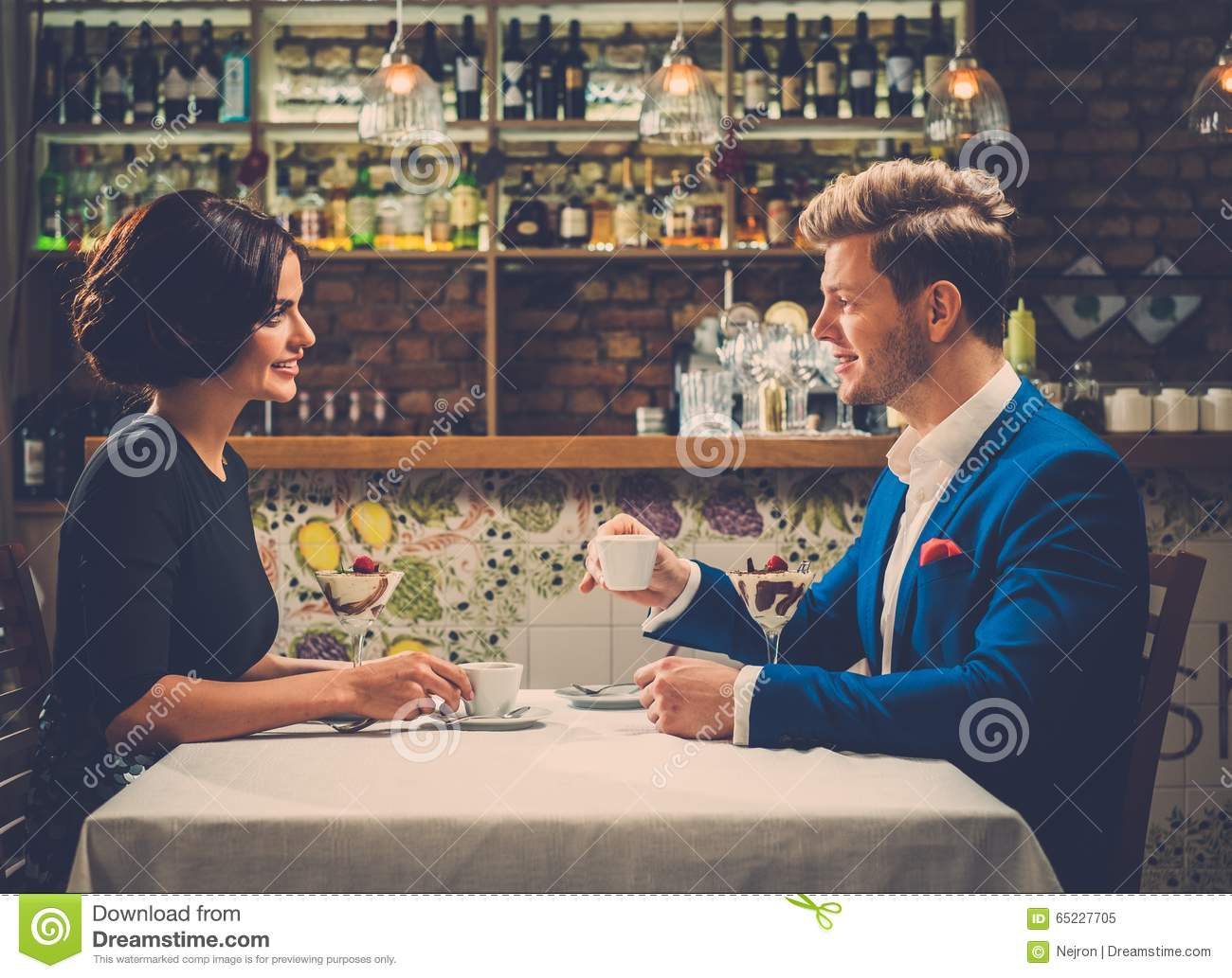 Stylish wealthy couple having desert and coffee together