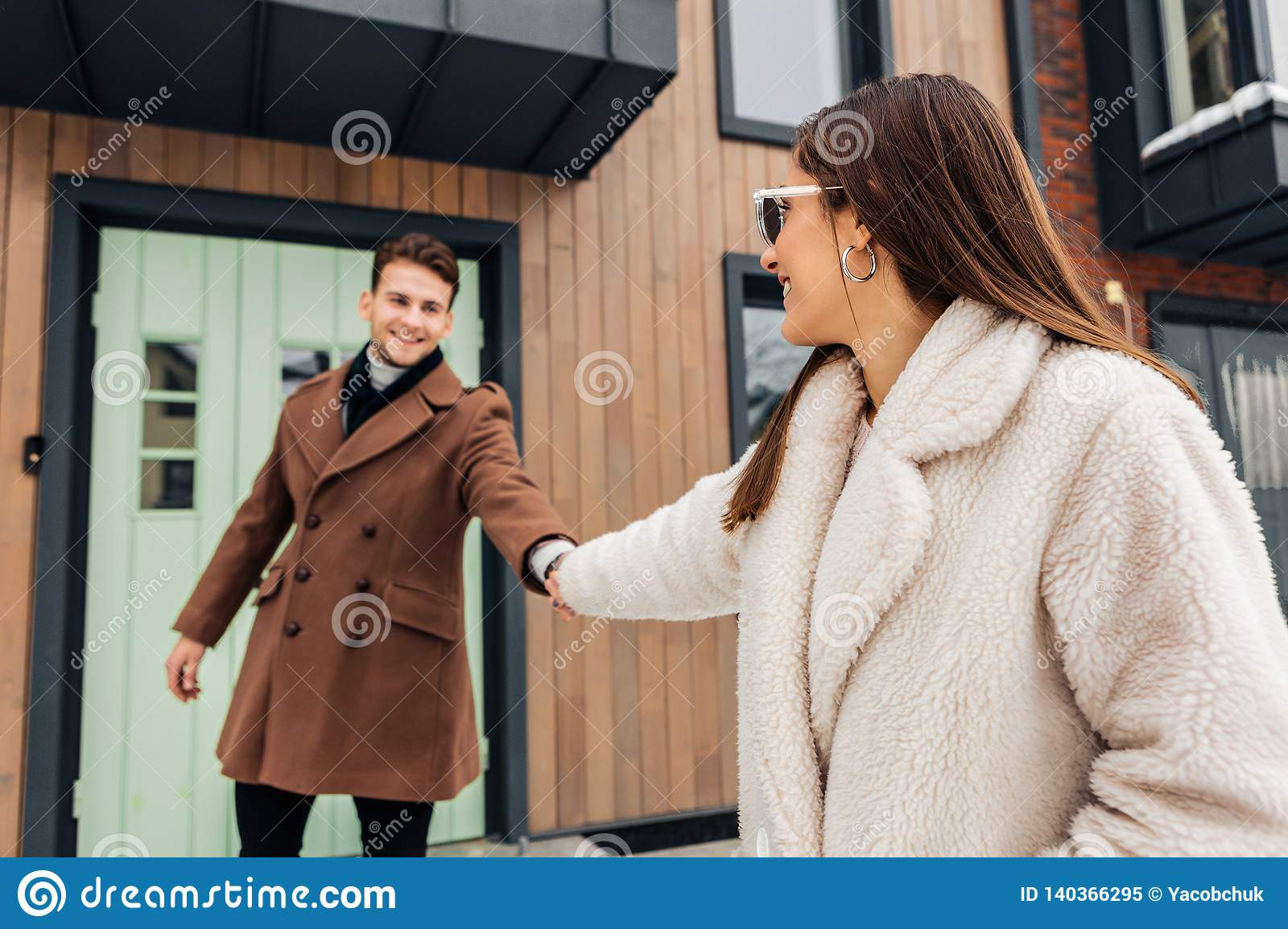 Stylish wife wearing warm beige coat asking her man to go for a walk