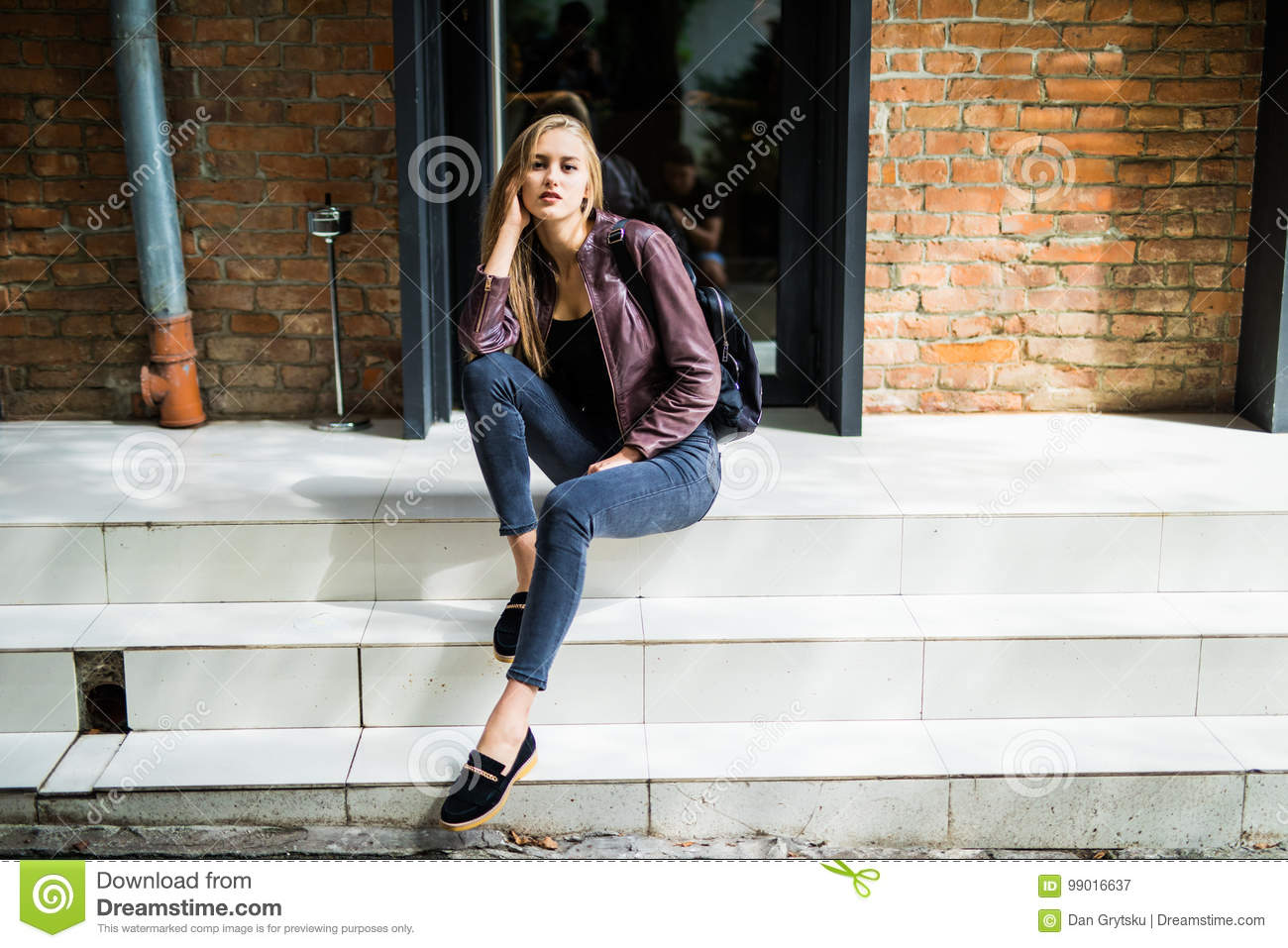 Casual style. Stylish woman in sunglasses sitting on the stone stairs. She dressed in jacket, skinny jeans and shoes. Long hair, e