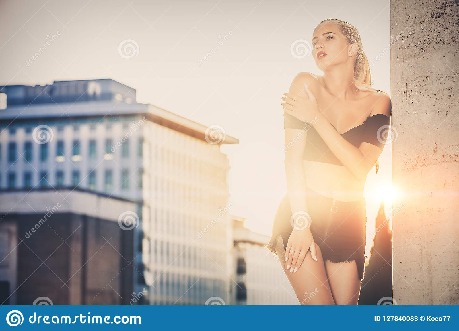 Stylish woman with urban sunset behind. Casual clothes, blonde hair and sensual attitude.