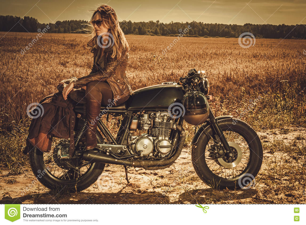 Stylish woman on the vintage custom cafe racer in a field.
