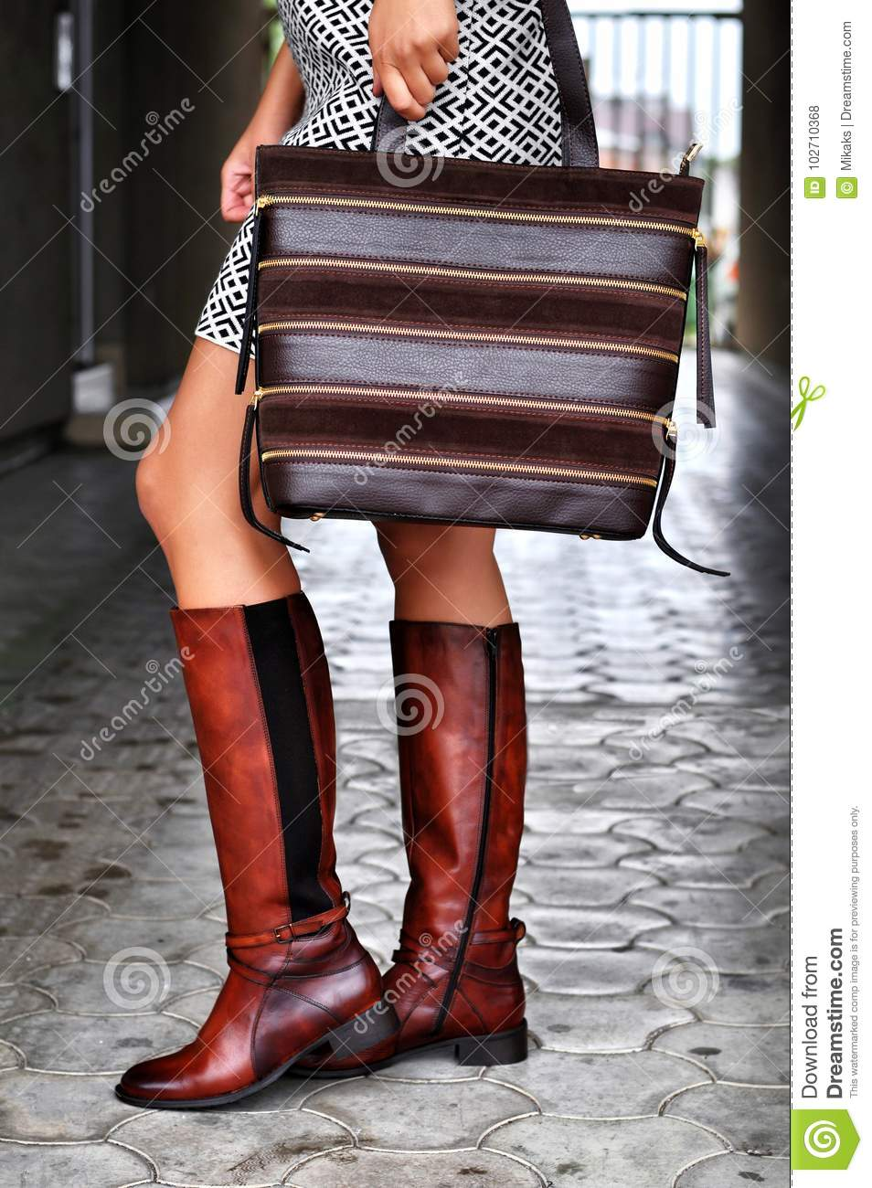Stylish Woman Walking In City Street Wearing Brown Leather Boots
