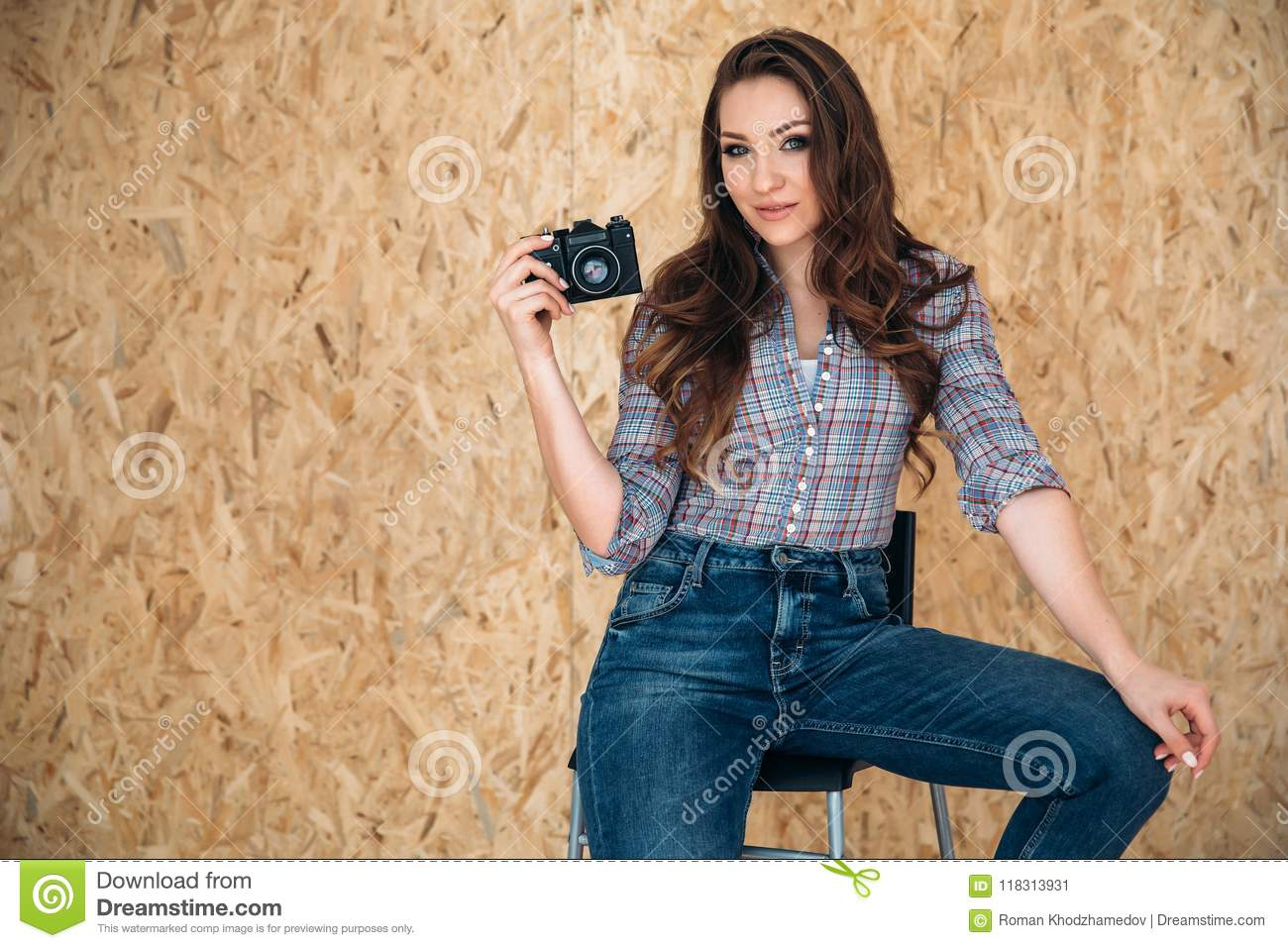 da8bececd553f A stylish young beautiful female model sits on a chair in a relaxed pose