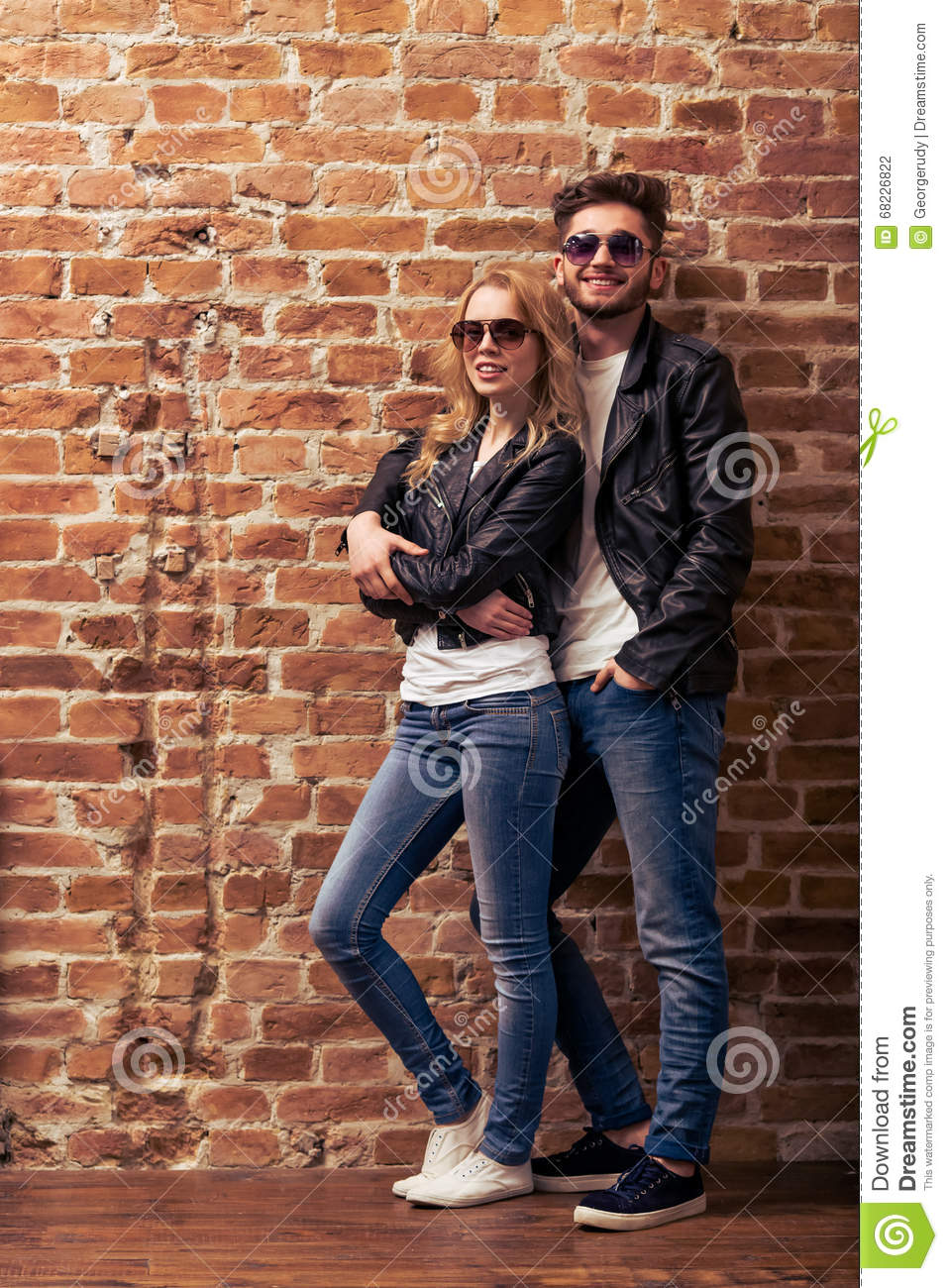 Cool Beautiful Young Couple In Leather Jackets And Sunglasses Is Looking At Camera Posing And Smiling Standing Against Brick Wall