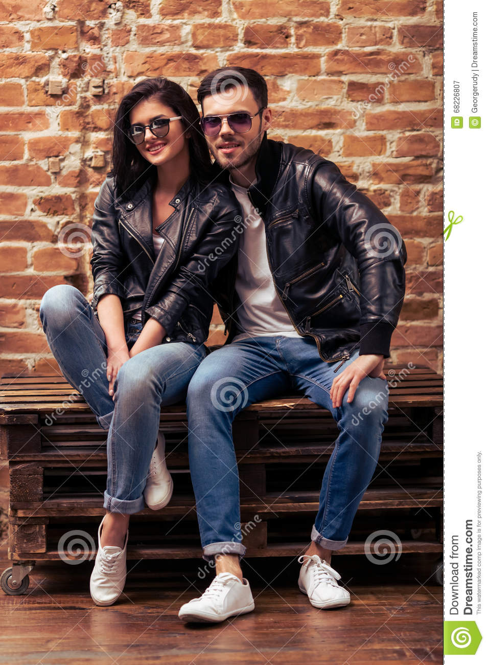 Cool Beautiful Young Couple In Leather Jackets And Sunglasses Is Looking At Camera And Smiling Sitting Against Brick Wall