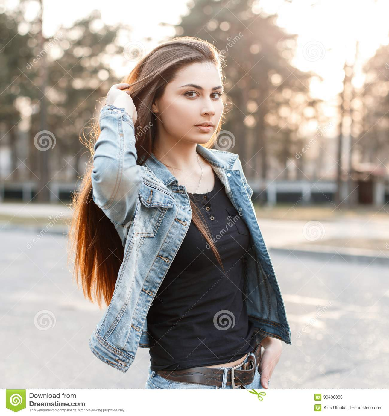 stylish young girl in fashionable jeans clothes corrects her lon
