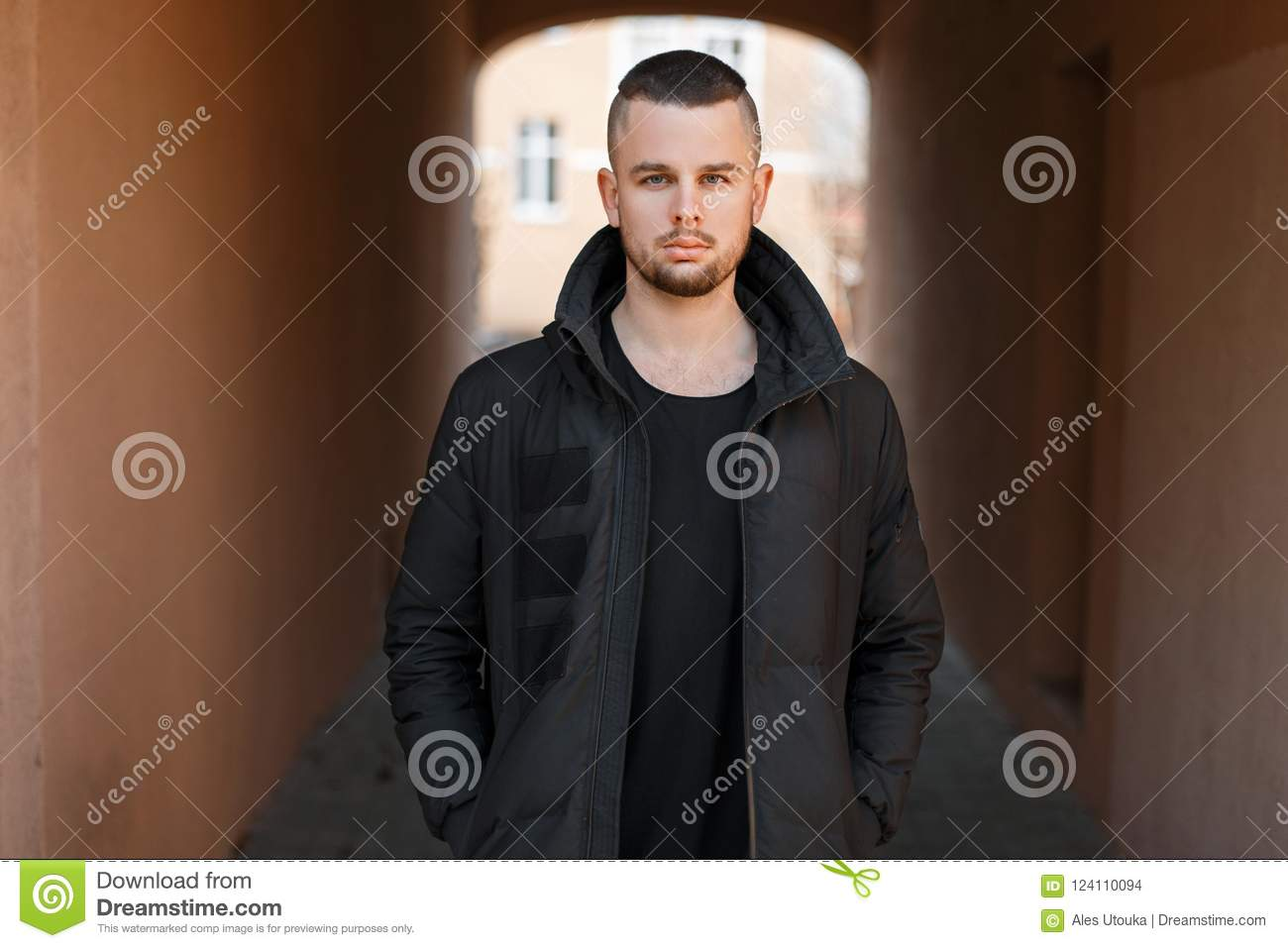 40c8e662e90d Stylish young handsome man with a short haircut in a black fashion winter  jacket stands on the street