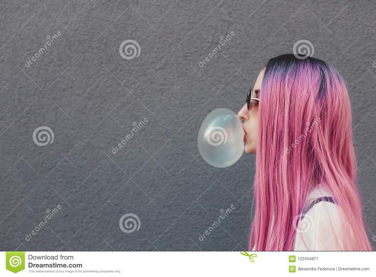 Stylish young hipster woman with long pink hair blowing a bubble with bubble gum.