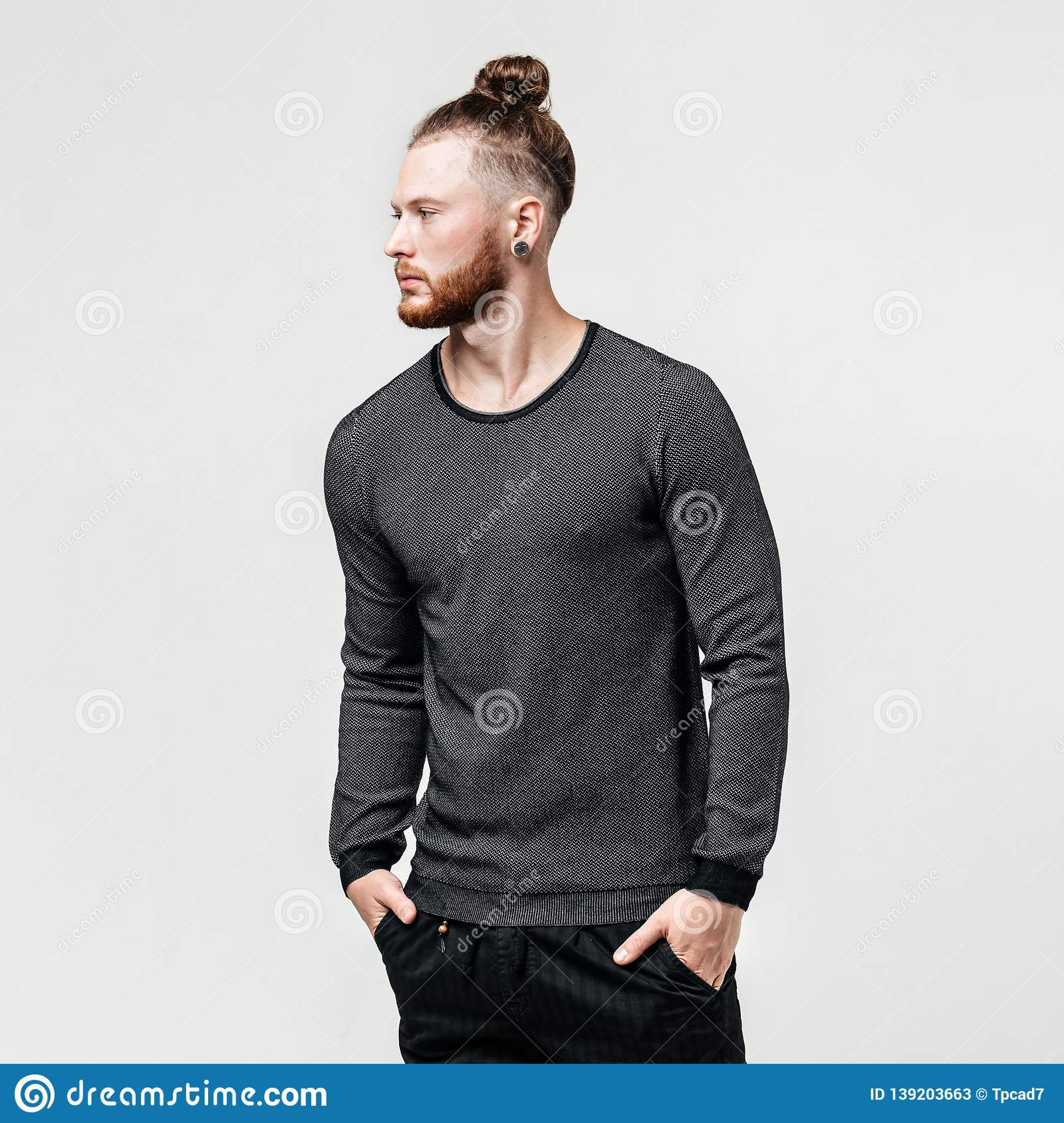 7c67b0fed Stylish young man with beard and bun hairstyle wearing a gray jumper and  black trousers poses in the studio on the white background .