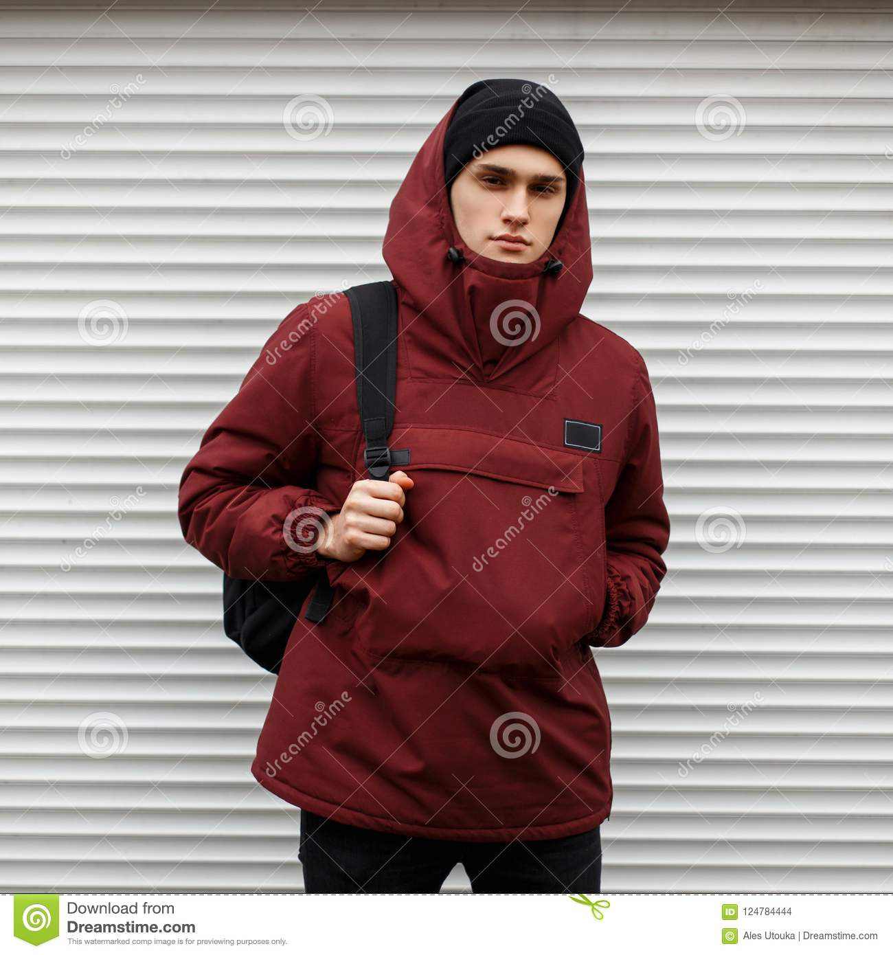 99244d48 Stylish young man in a fashionable winter red sports jacket with a cap of a  white metal wall on the street
