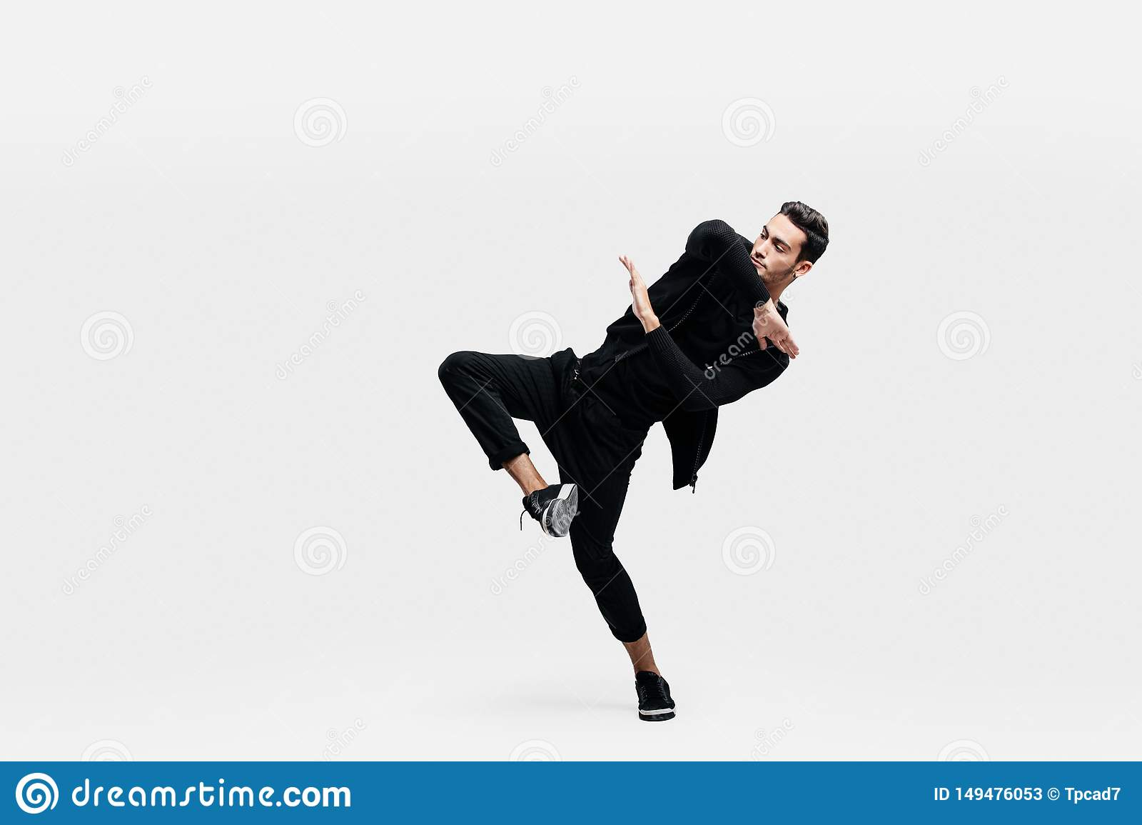 Stylish young man wearing a black sweatshirt and black pants makes stylized movements of hip-poh