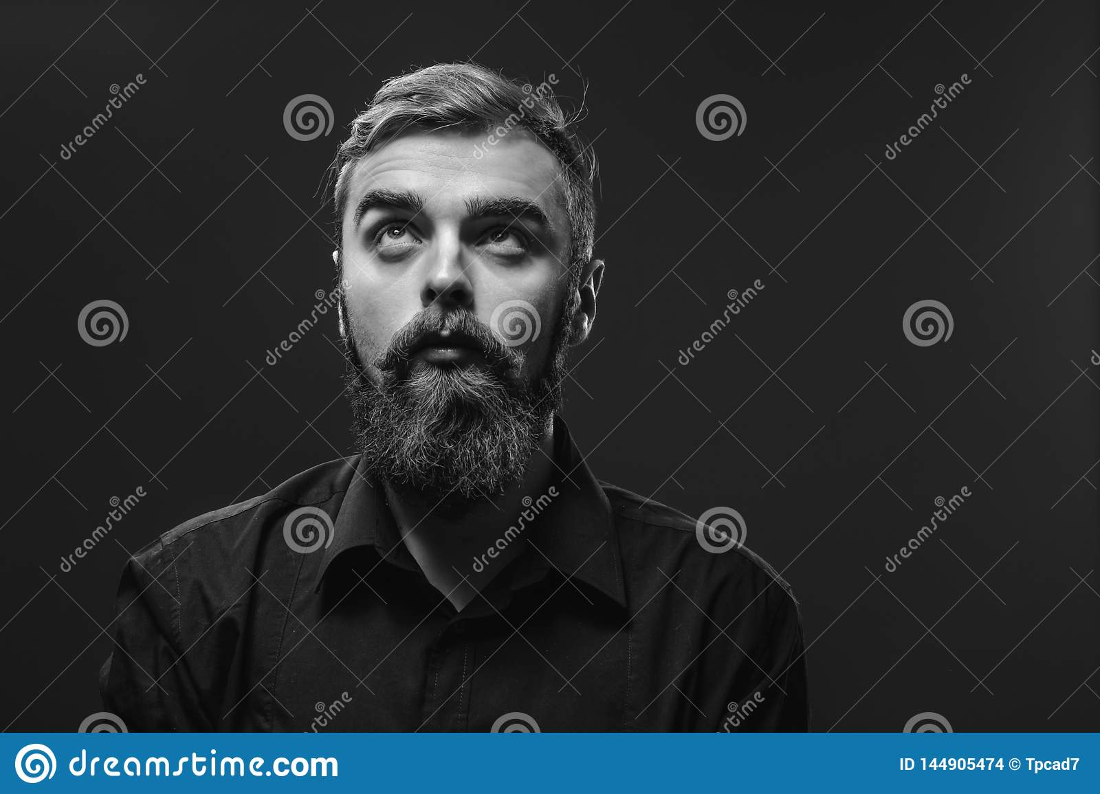 Stylish young red-haired man with a beard and mustache dressed i