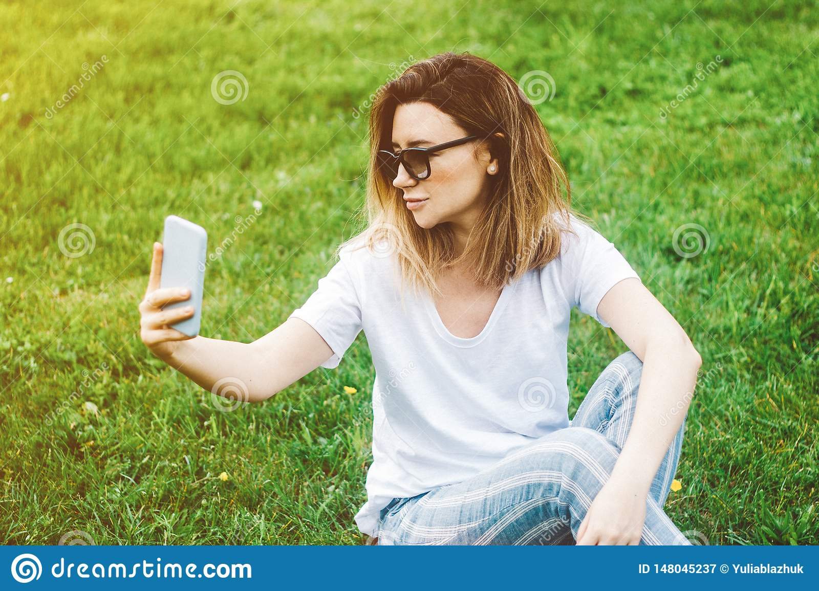 Stylish young woman making selfie in the park with a smartphone