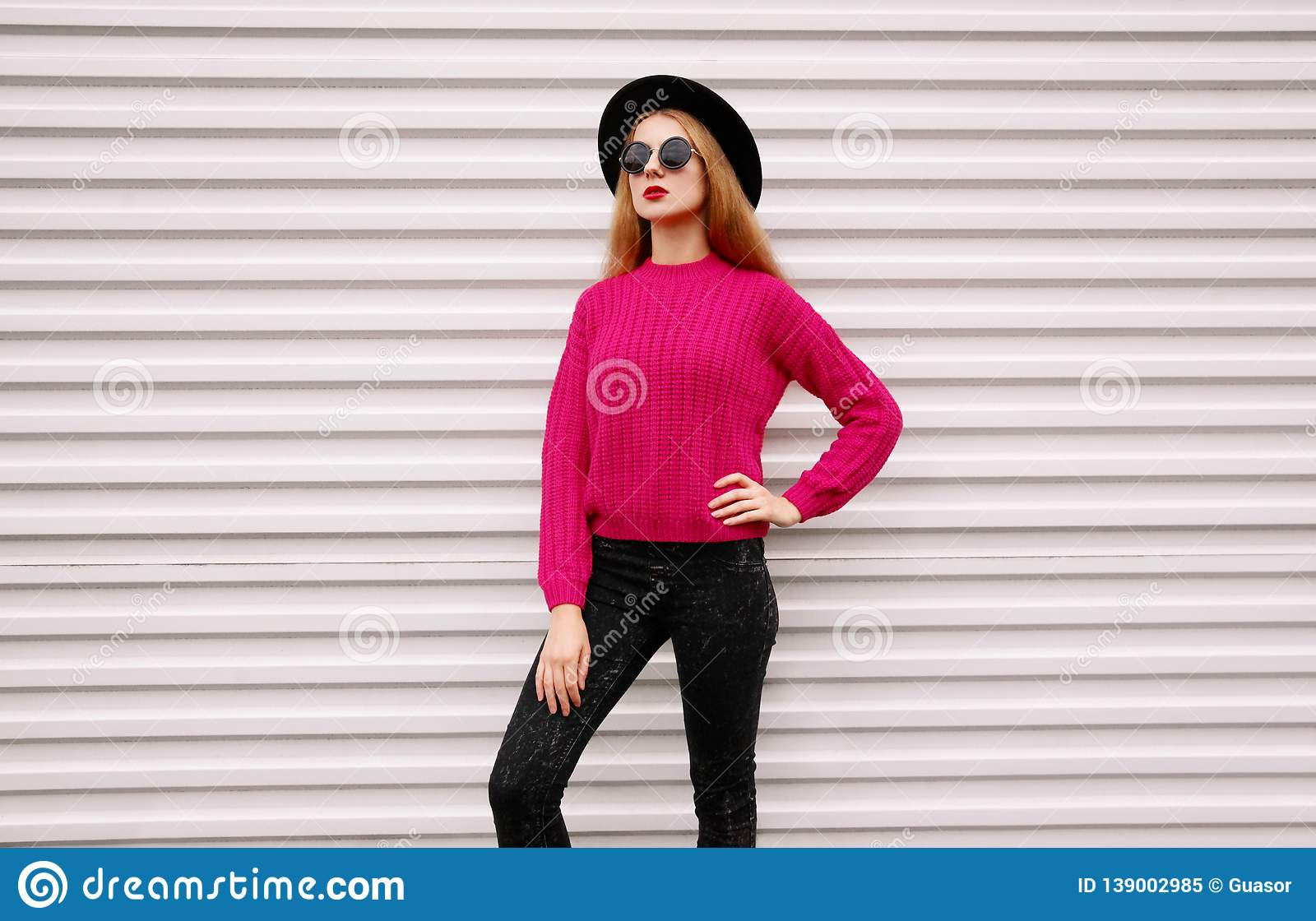 Stylish young woman posing in colorful pink knitted sweater, black round hat on white wall