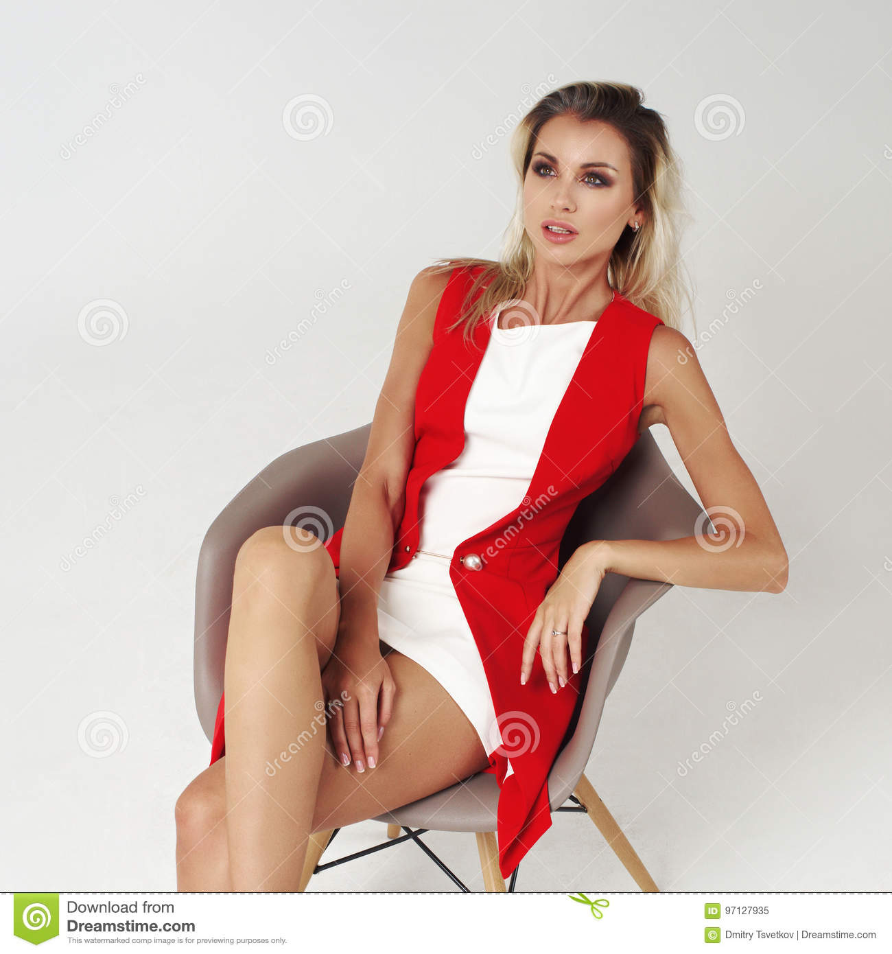 Stylish young woman in white dress and red jacket