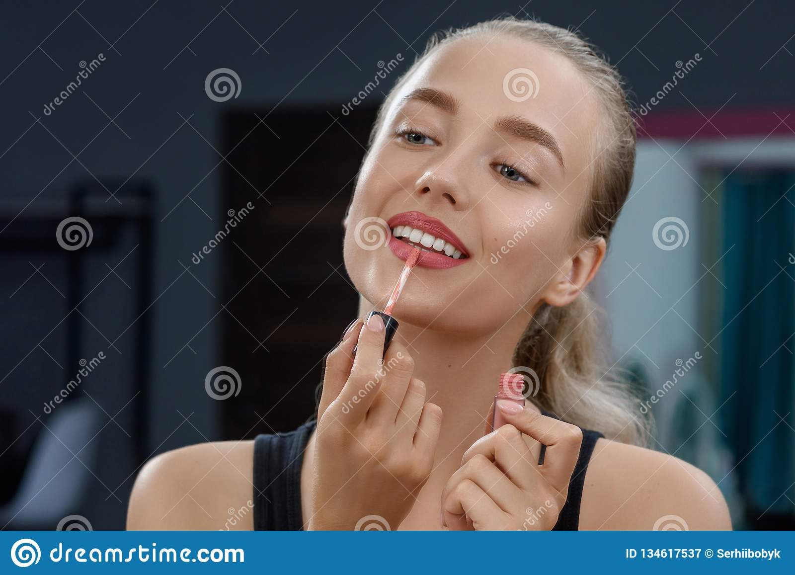 Stylist keeping lipstick and doing makeup.