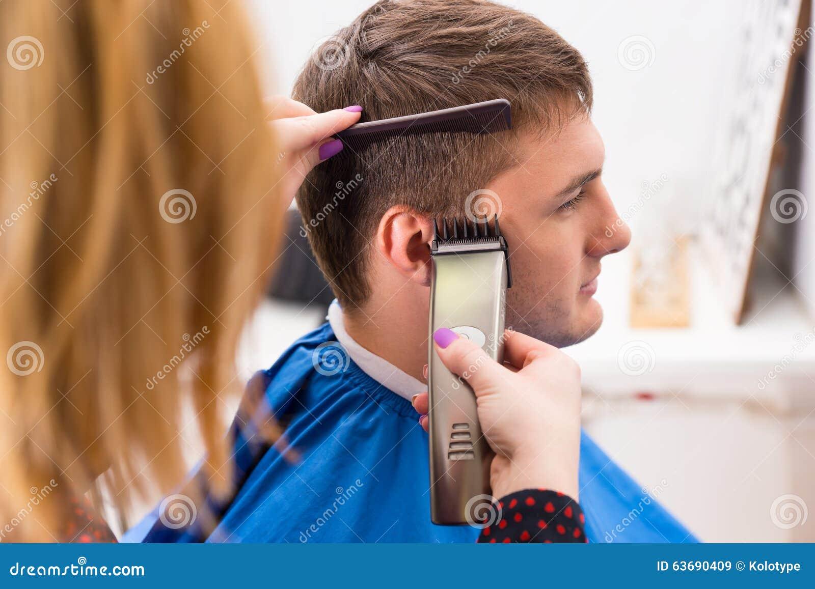 Styliste à l aide du rasoir pour couper des cheveux du client masculin