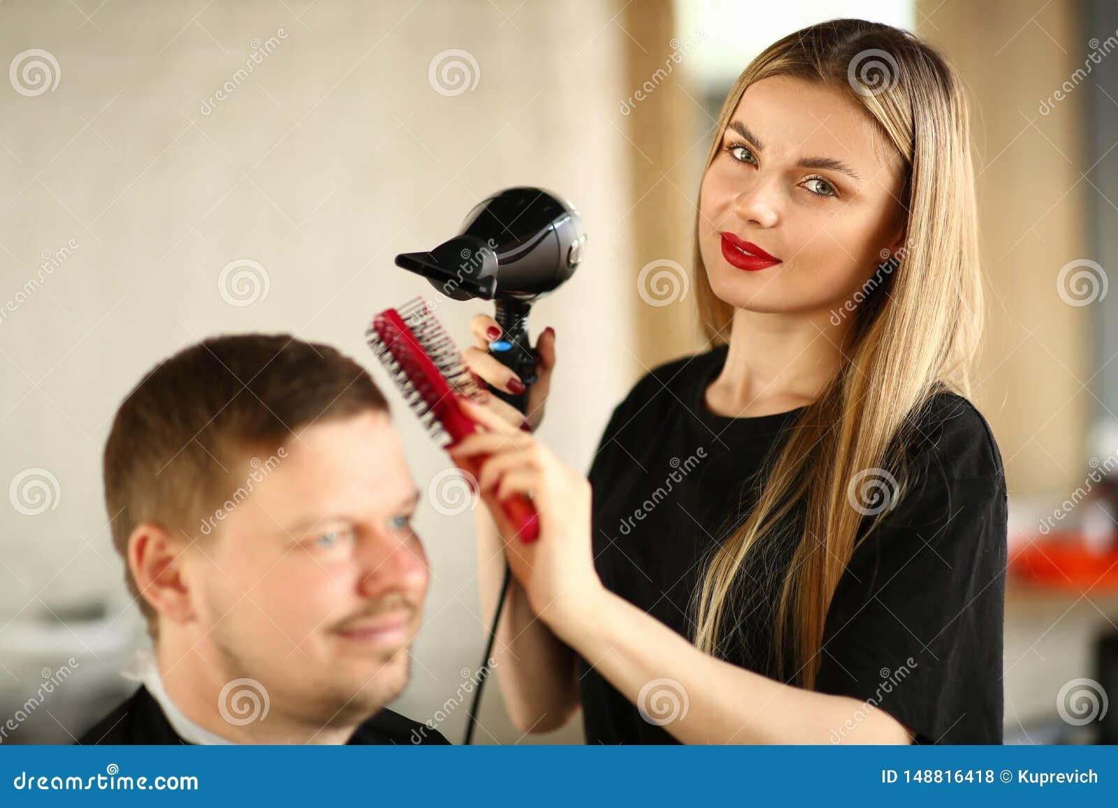 Styliste en coiffure dénommant la coiffure avec le dessiccateur et le peigne