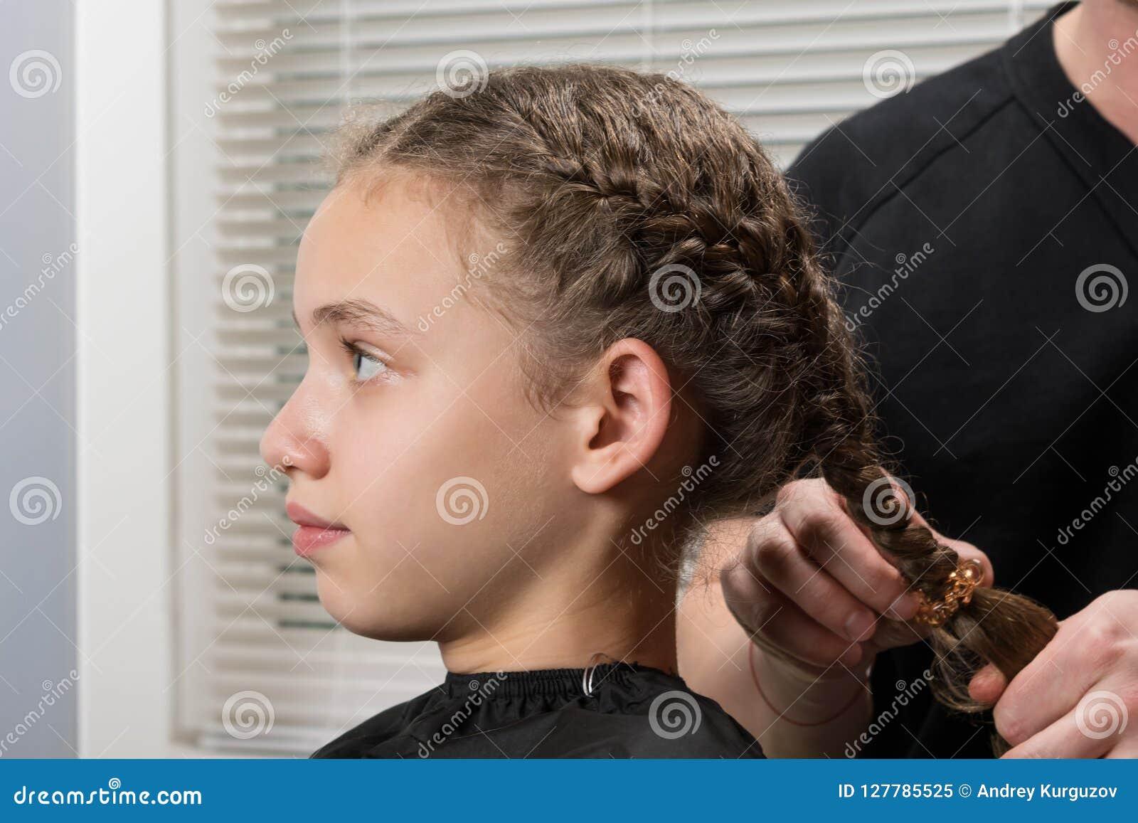 Stylisten gör flickan en flätad tråd för hår, närbild