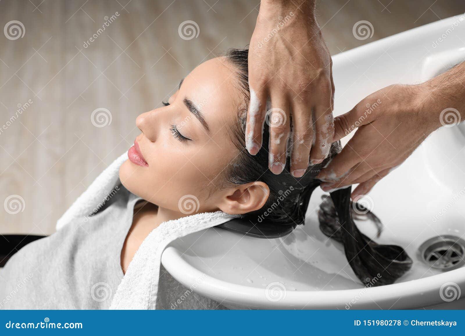 Stylisttvagningklients hår på vasken