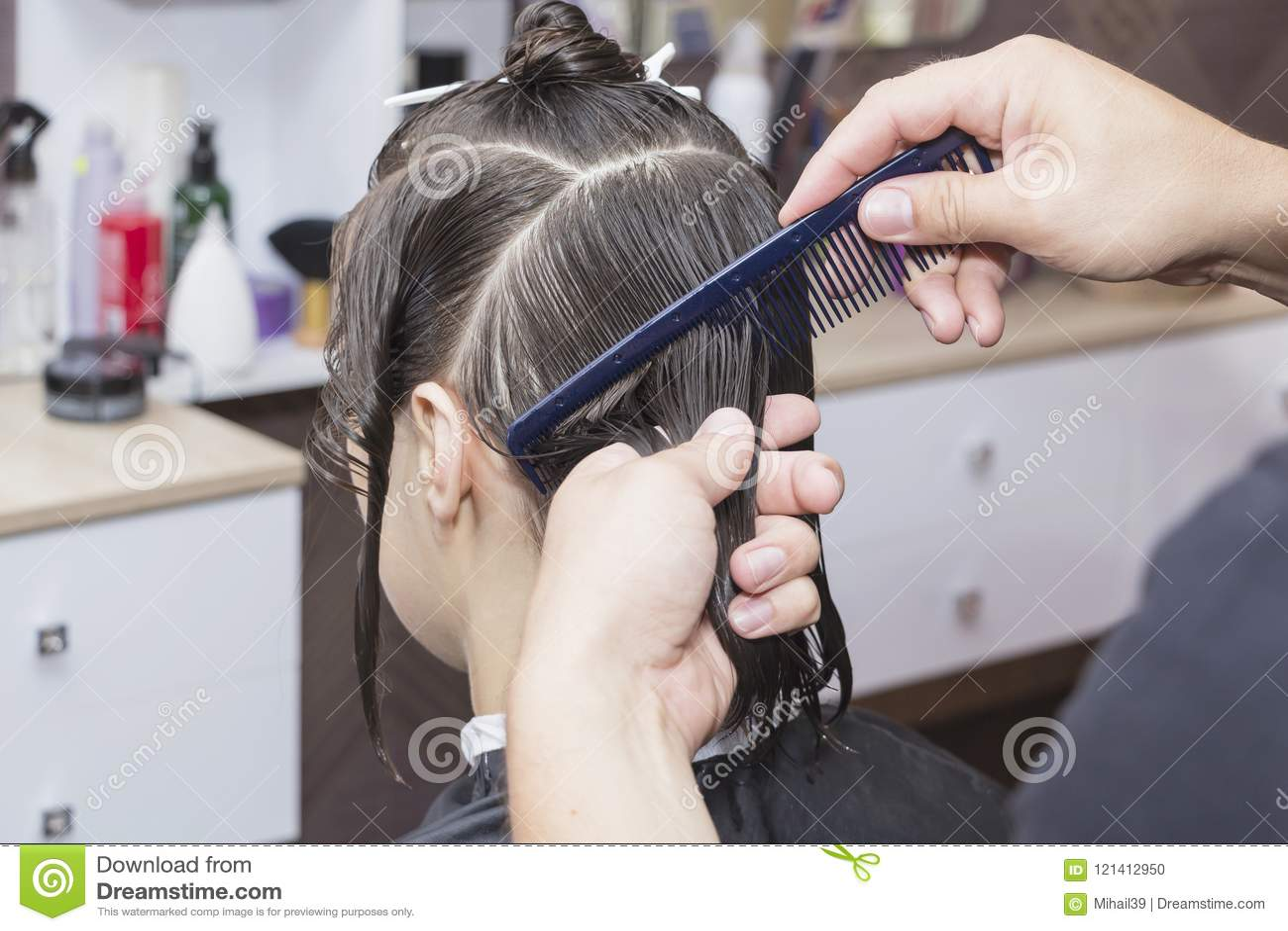 Stylisty fryzjer w fryzjera męskiego sklepie robi ostrzyżenia zbliżeniu
