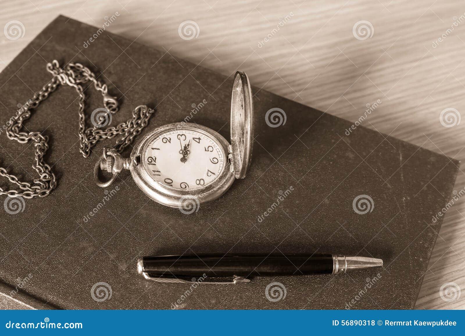 Stylo et horloge sur des livres