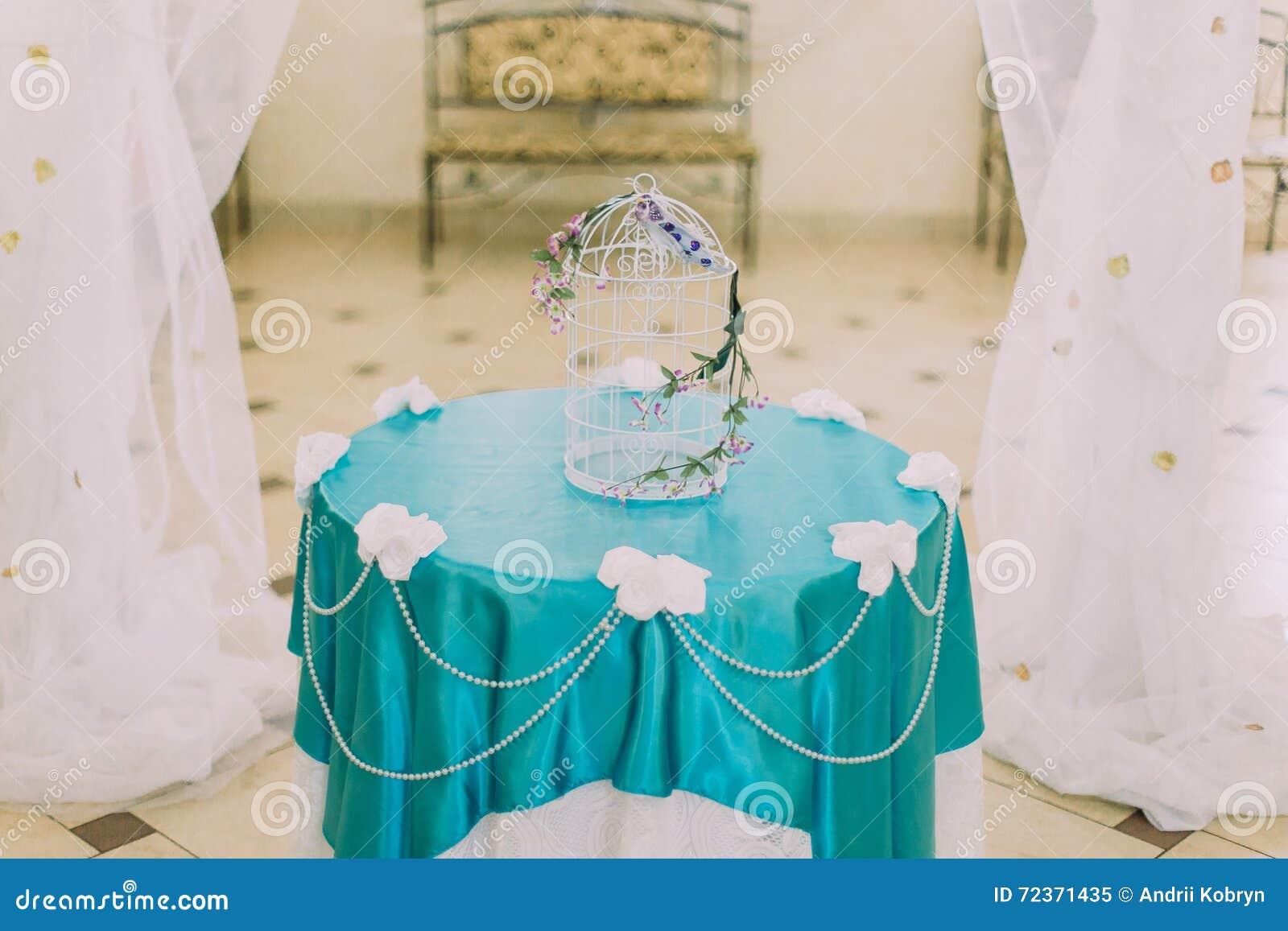 与一些逗人喜爱的花的美丽的装饰鸟笼在stylysh在两幅帷幕之间的葡萄酒内部