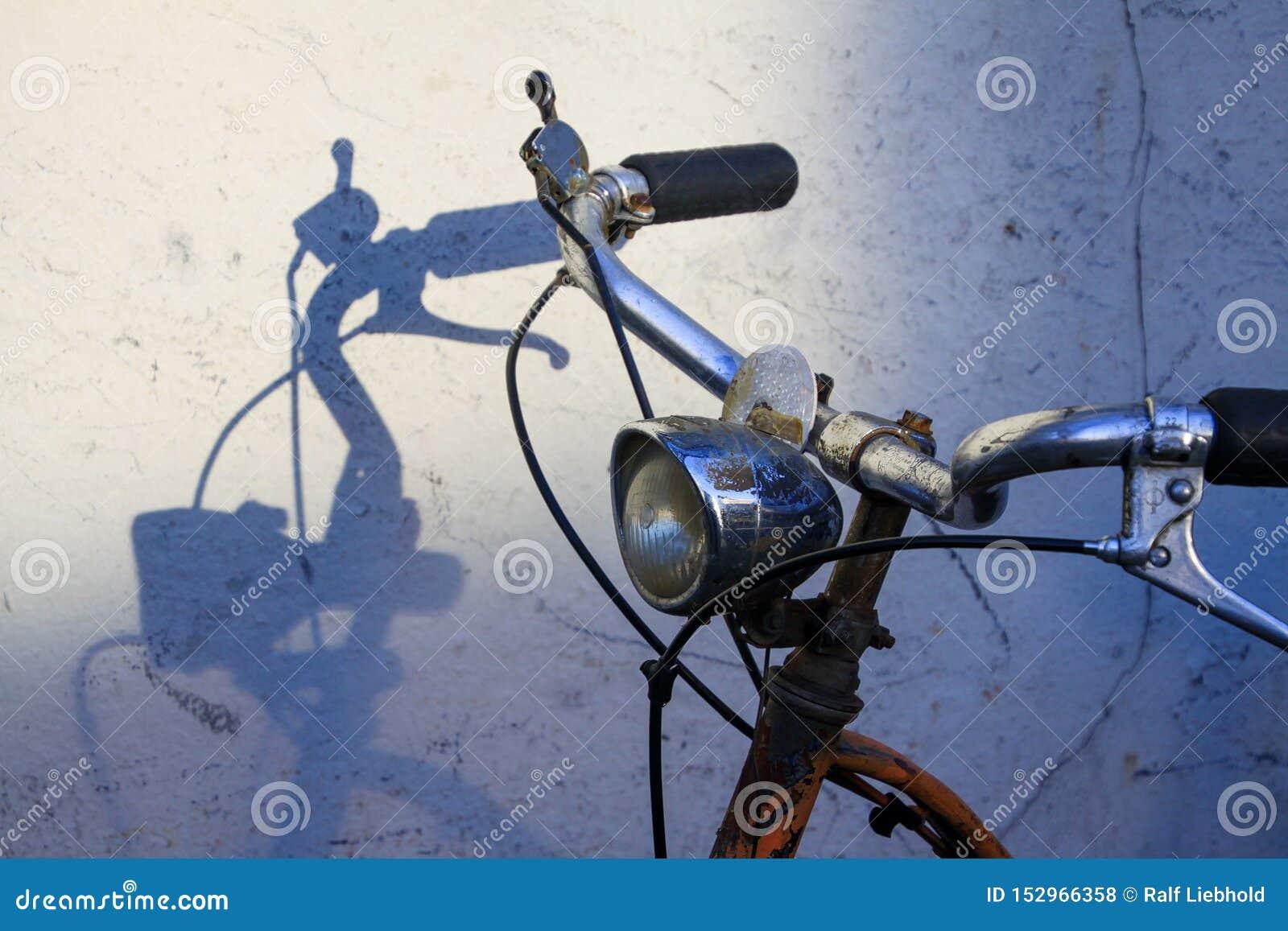 Styren av den gamla rostiga cykeln som kastar skuggor på den vita väggen