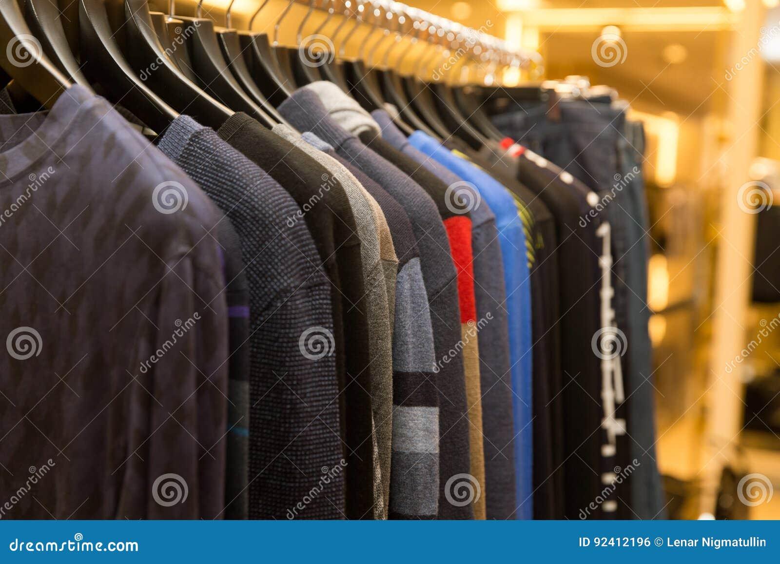 Suéteres y camisas de los hombres en diversos colores en suspensiones en  una tienda al por 3f66a420571a