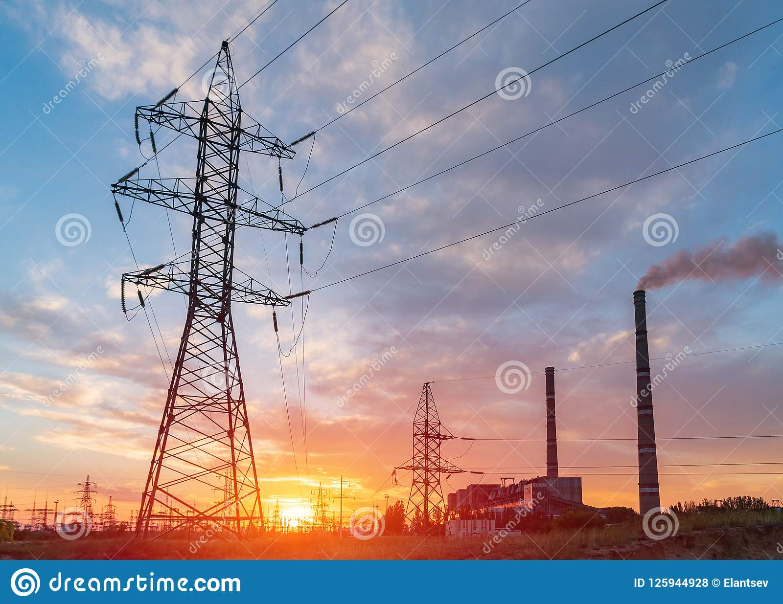 Subestação elétrica da distribuição com linhas elétricas e transformadores, no por do sol