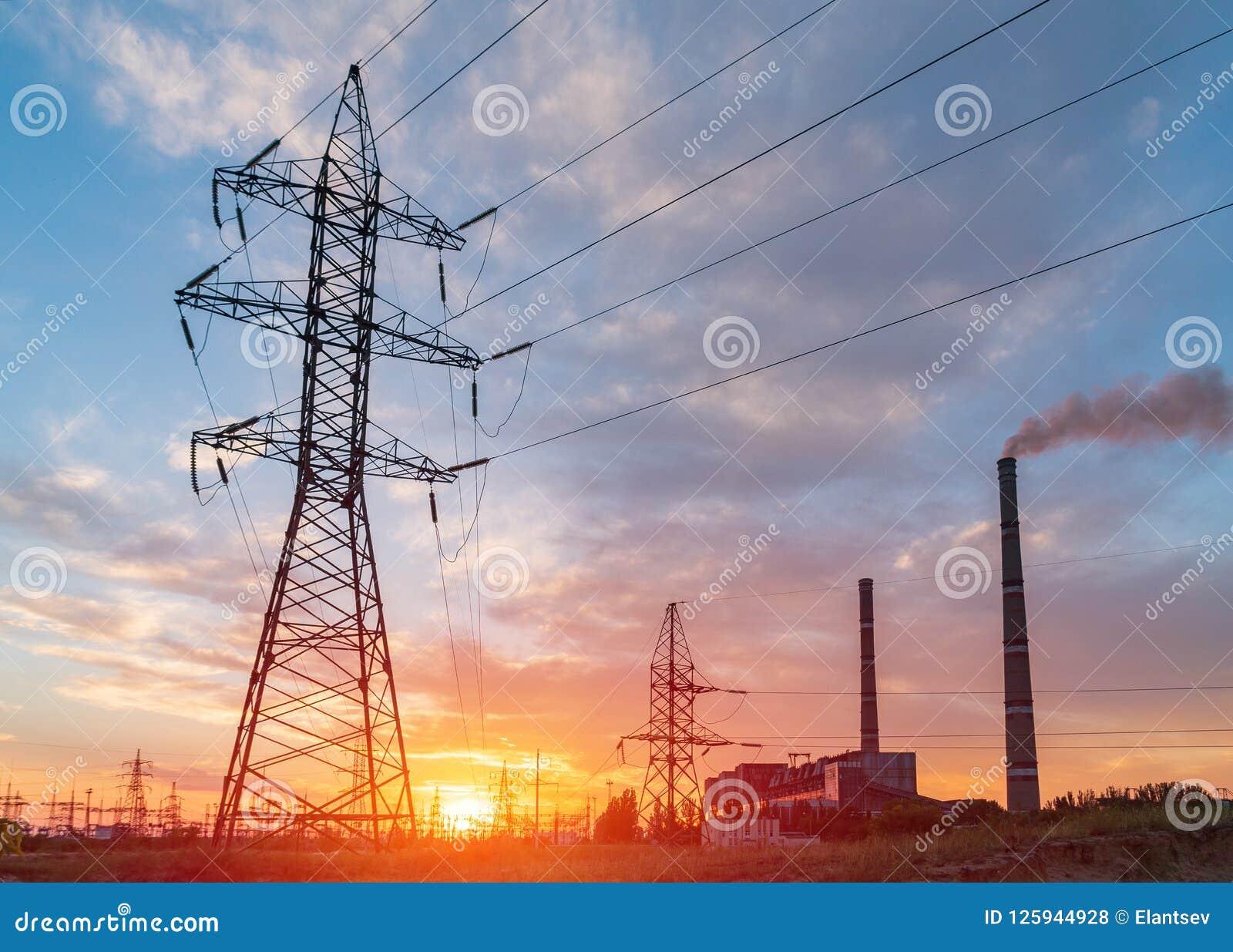 Subestación eléctrica de la distribución con las líneas eléctricas y los transformadores, en la puesta del sol
