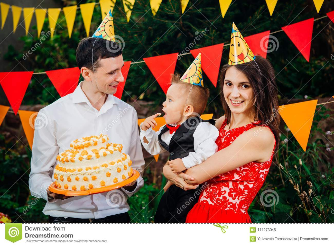 Subject Childrens Birthday Party Food And Sweets A Young Family Celebrates One Year Of Son Dad Is Holding Big Cake Mom Baby In Her Arms