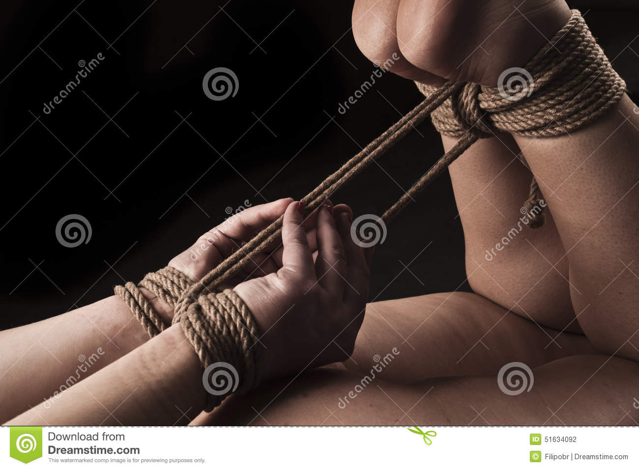 Submissive Woman In Hog Tie Bondage Position On Black Background