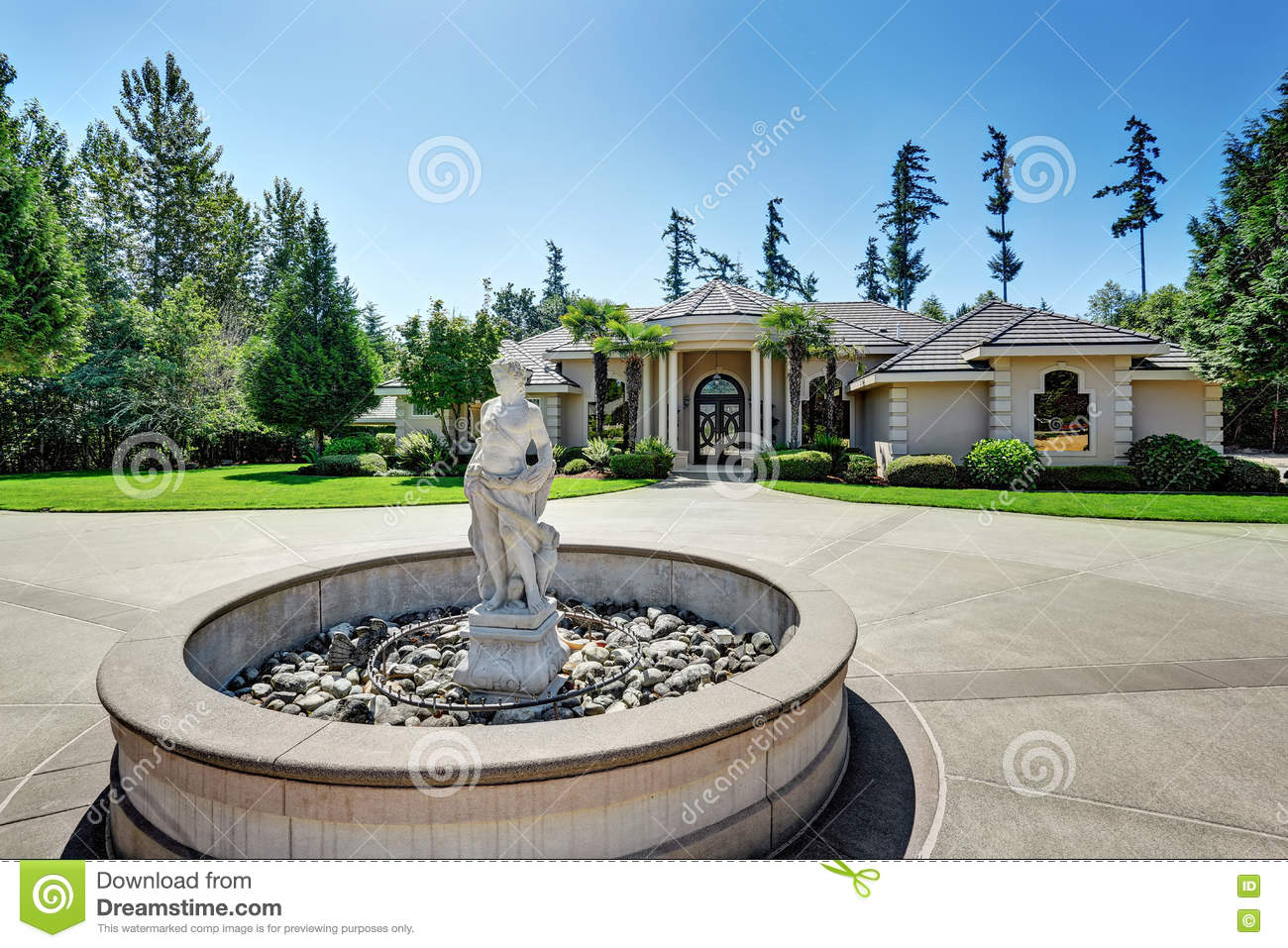 suburban luxury house fountain statue front yard family asphalt driveway residential large windows trees 77540478