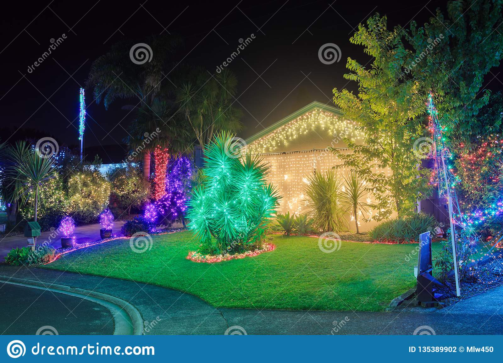 Colorful Christmas Lights On House.House And Garden Brightly Lit With Multicolored Christmas