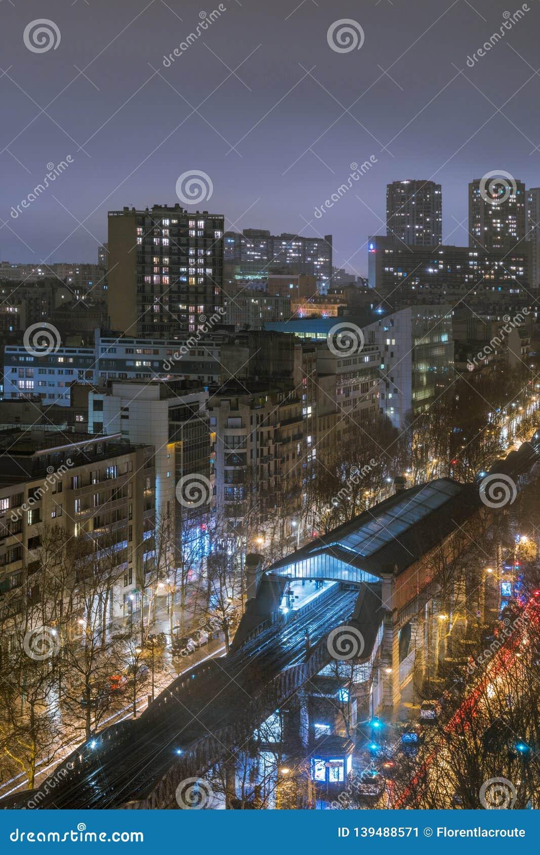 Subway station on a bridge at night in Paris, France