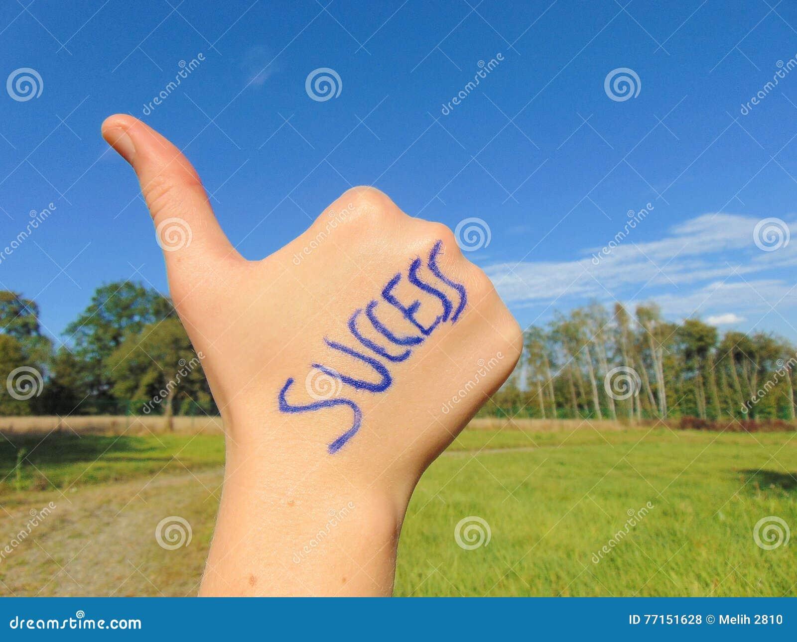 Succès écrit en main avec le pouce